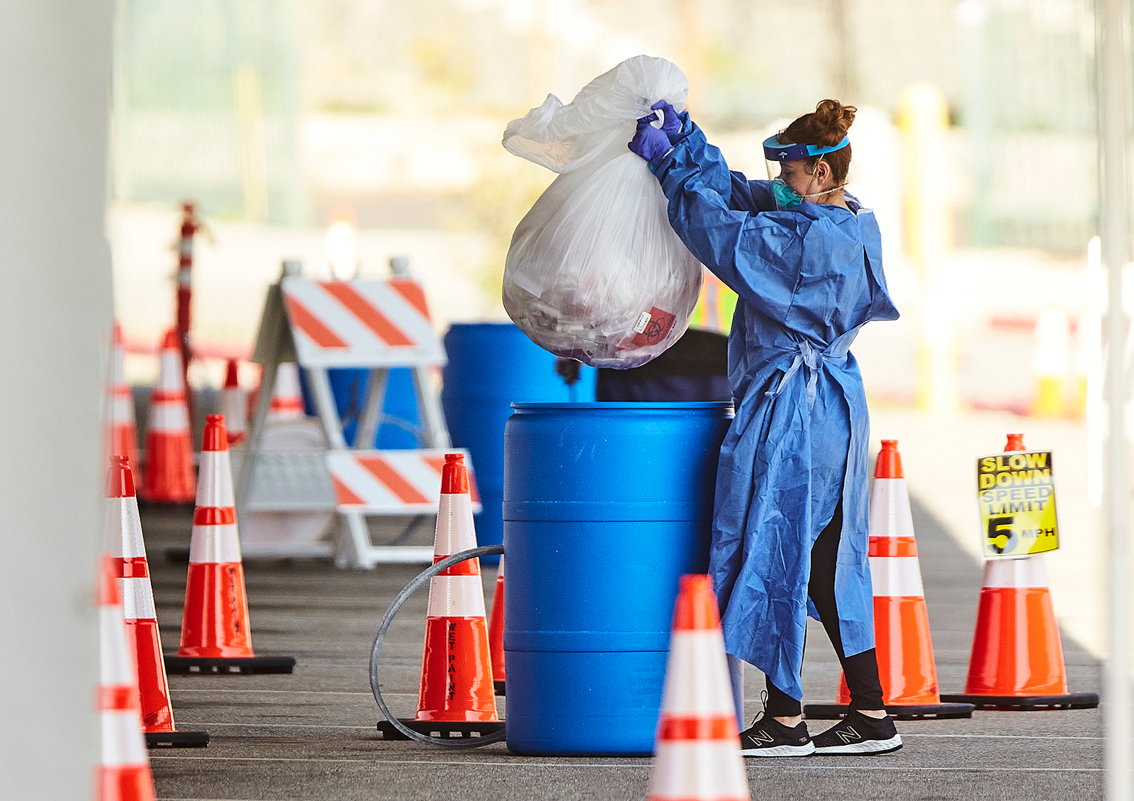 A medical worker wearing protective gear collects testing kits used by motorists at a coronavirus drive-up testing site at East Los Angeles College on April 30.