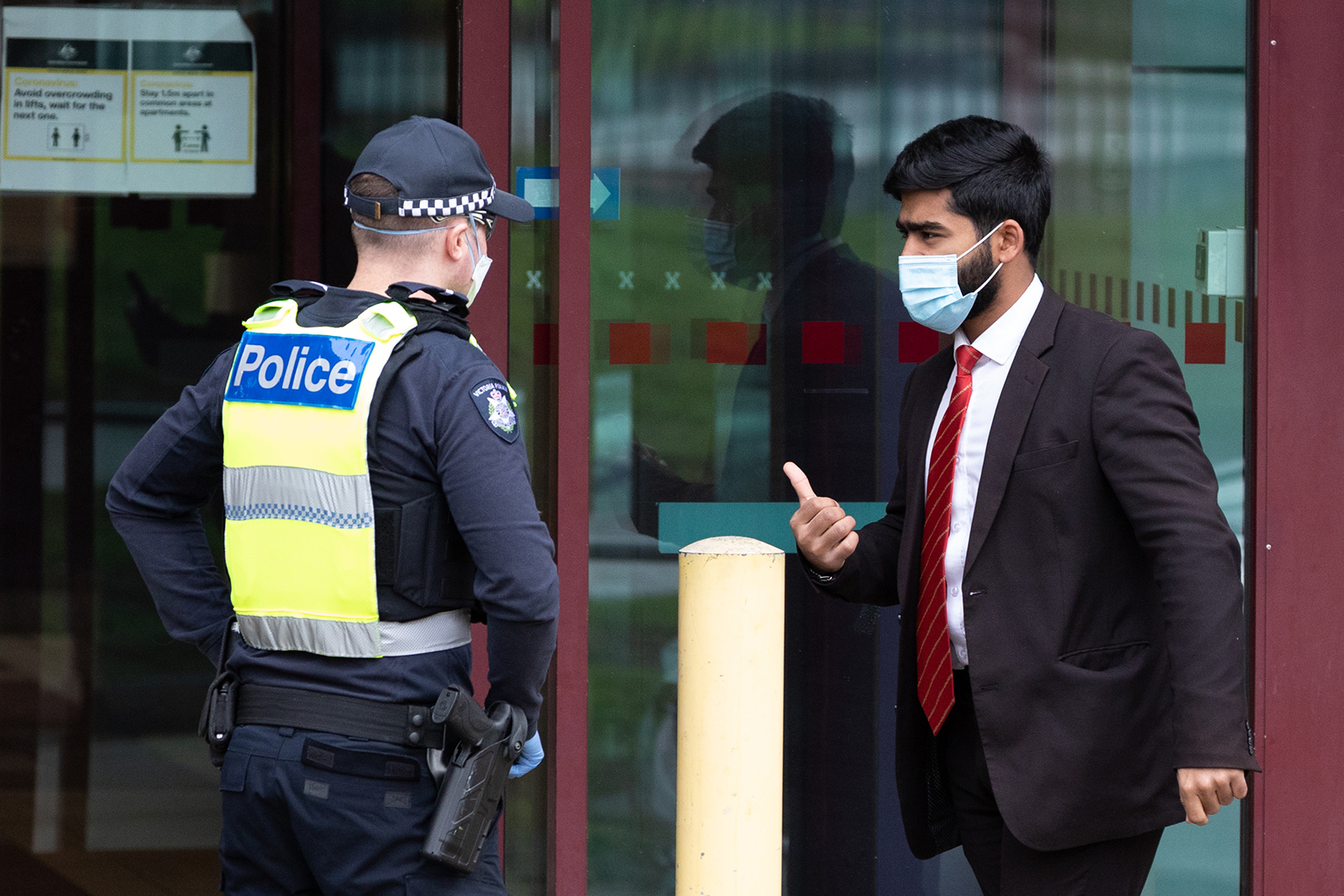 Police speak to a man outside the North Melbourne Public housing flats on July 5, in Melbourne, Australia.