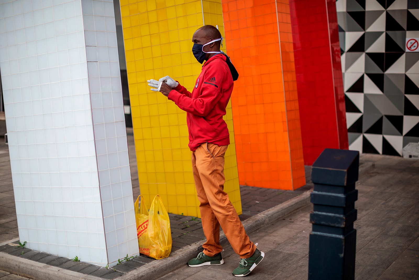 A man wearing a face mask puts on a pair of gloves at the entrance of a shopping mall in Alexandra, Johannesburg, South Africa on April 10.