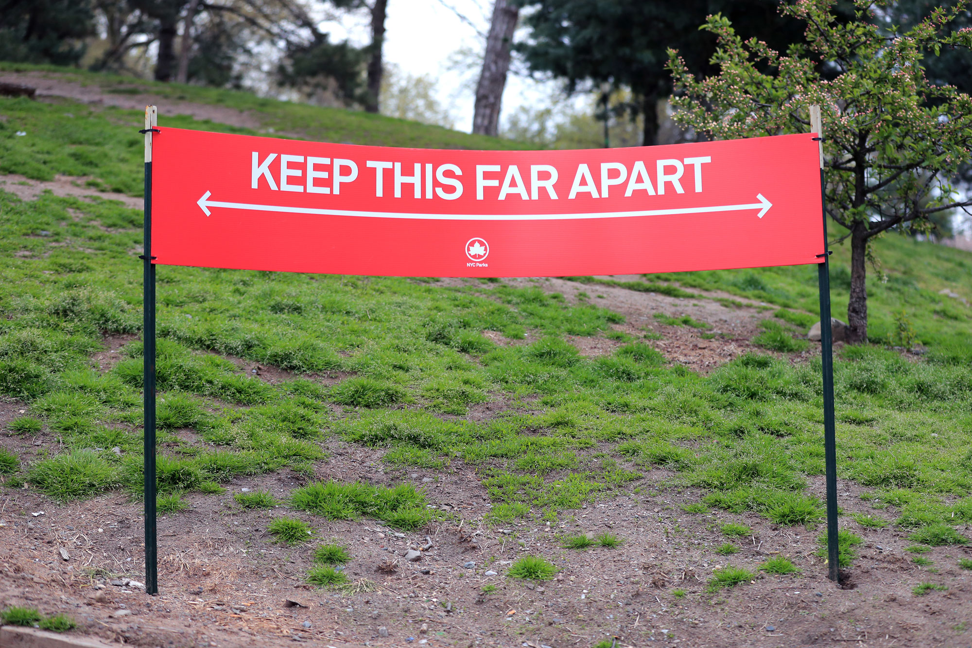"""A social distance guideline sign stating """"Keep This Far Apart"""" is seen in Fort Greene Park on April 23, in the Clinton Hill neighborhood of the Brooklyn borough of New York City."""