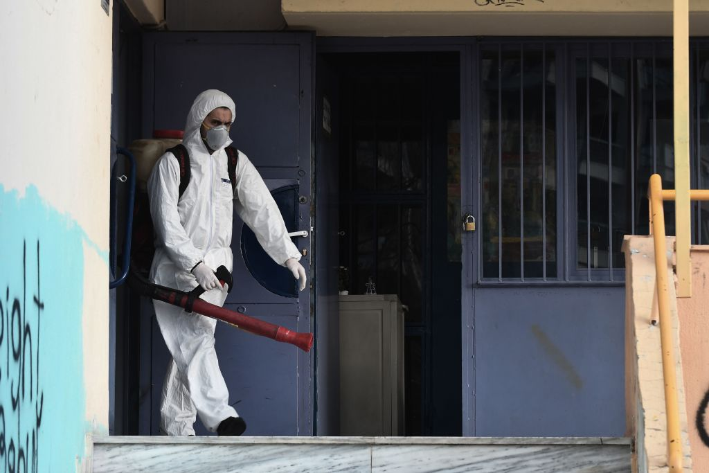 A worker walks out as he sprays disinfectant as part of preventive measures against the spread of the COVID-19, the novel coronavirus, in a school in Thessaloniki, northern Greece, on February 27, 2020.