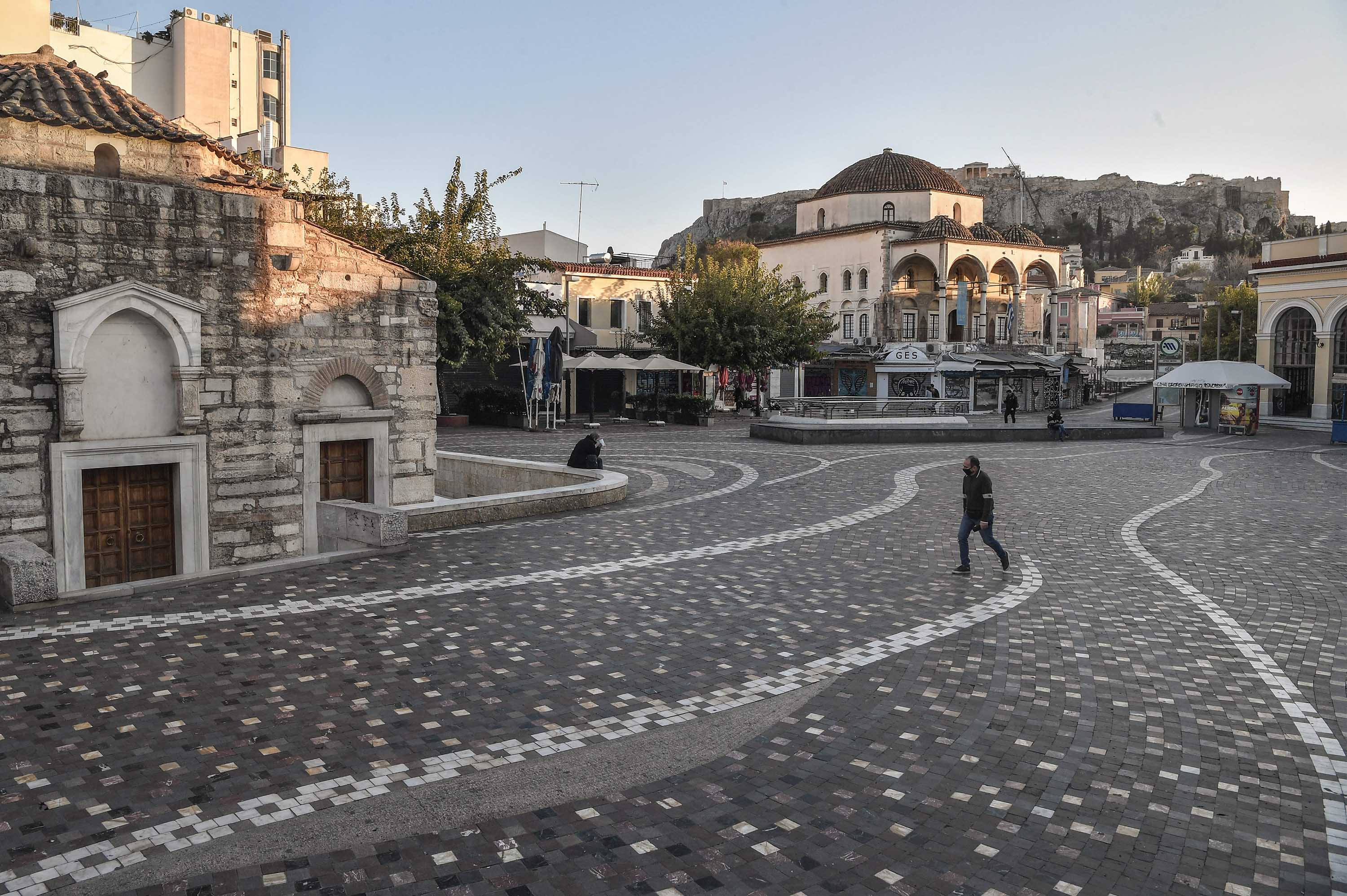 A person walks past a nearly empty square in Athens, Greece, on December 1.