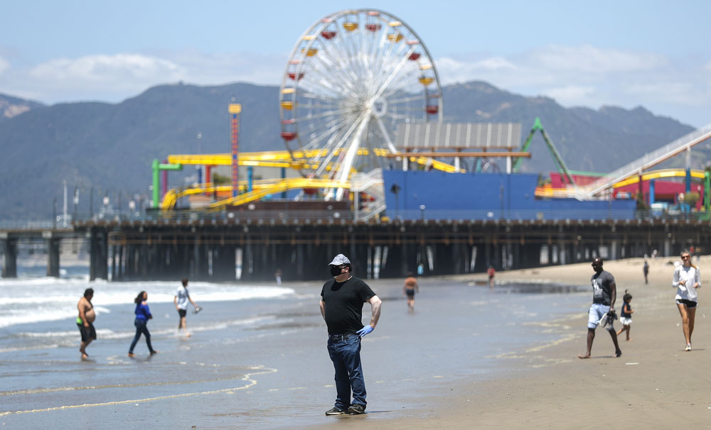 A man wears a face mask and gloves on Santa Monica beach on the day Los Angeles County reopened its beaches, which had been closed due the coronavirus pandemic, on May 13 in Santa Monica.