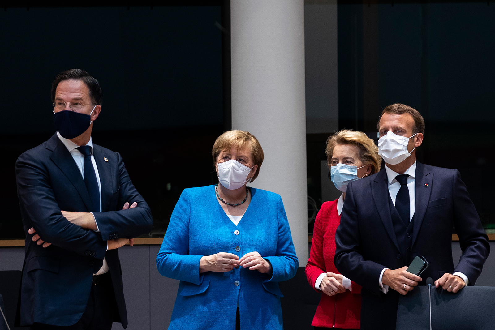 Netherlands' Prime Minister Mark Rutte (left) looks on next to Germany's Chancellor Angela Merkel (2nd from left), President of the European Commission Ursula von der Leyen (2nd from right) and France's President Emmanuel Macron (right) prior the start of the European Council building in Brussels, on July 18.