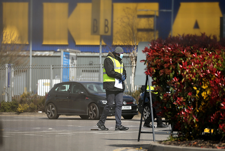 Britain's NHS workers wait in their cars to be tested for COVID-19 at a drive-in facility set up in the car park of an IKEA store in Wembley, north-west London on Tuesday, March 31.