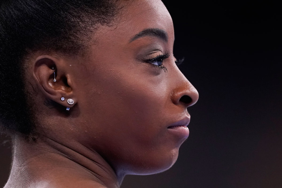 Simone Biles stand on the mat during the warm up prior to the artistic gymnastics balance beam final.