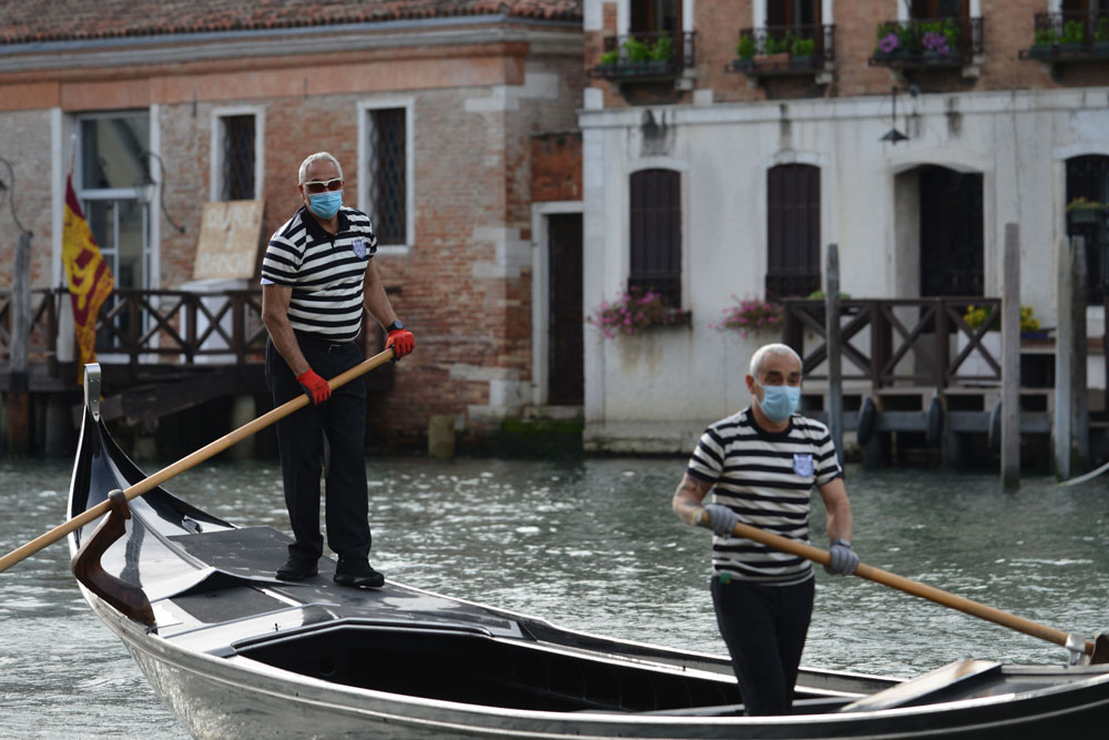 Gondoliers wearing a face mask ride a gondola by the San Toma embankment on a Venice canal as they resume service on May 18.