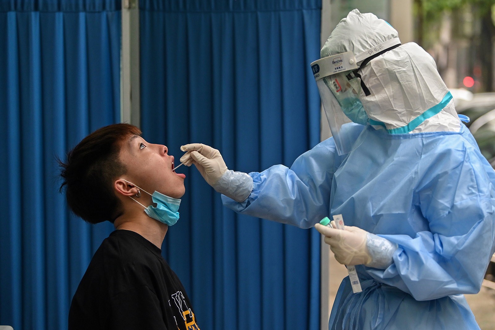 A medical worker takes a swab sample from a man to be tested for coronavirus in Wuhan, China on May 14.