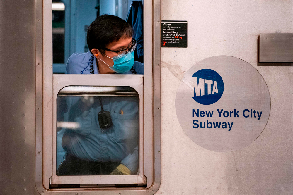A New York City Mass Transit Authority (MTA) transit worker looks down the platform from a subway car after arriving at the Coney Island station in Brooklyn, New York on May 6.