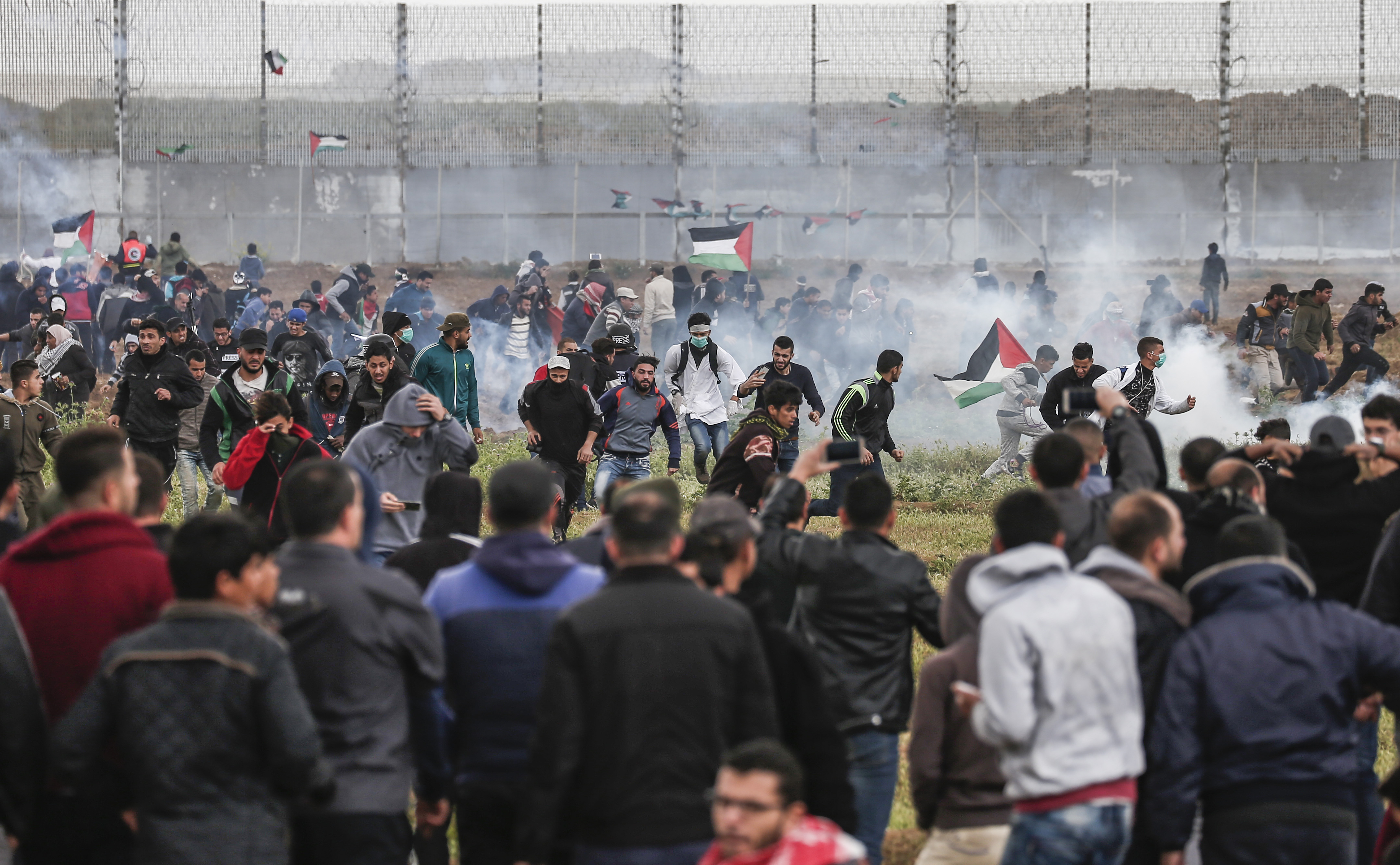 Protesters flee from tear gas fumes near the border with Israel in Malaka, east of Gaza City.