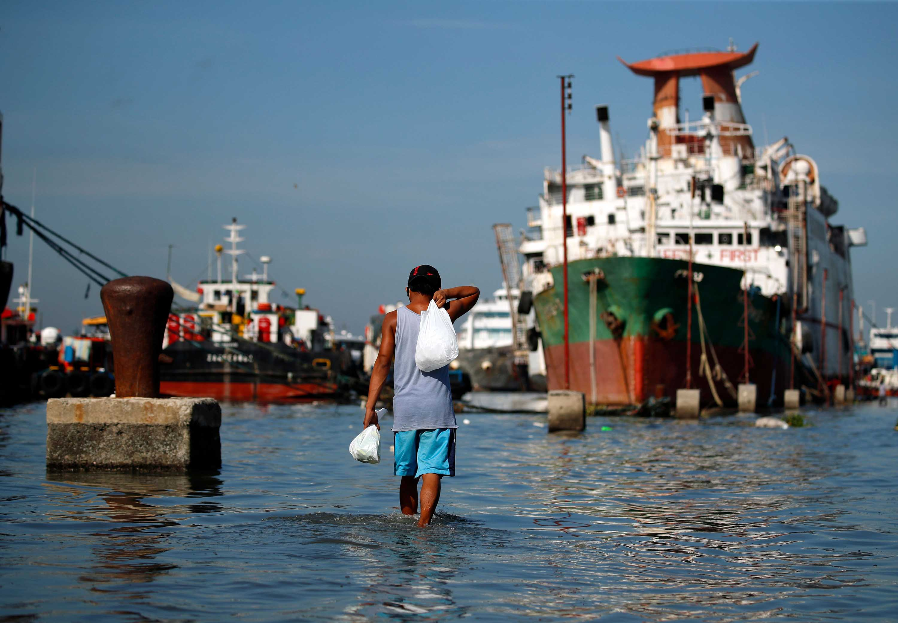 A fisherman wades in rising sea water at a port in Navotas city, Philippines, as a typhoon approached the region on May 14.