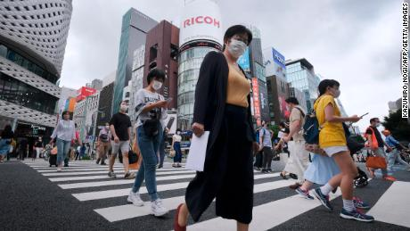 Pedestrians walk at a crossing in Tokyo's shopping district of Ginza on July 25, 2020