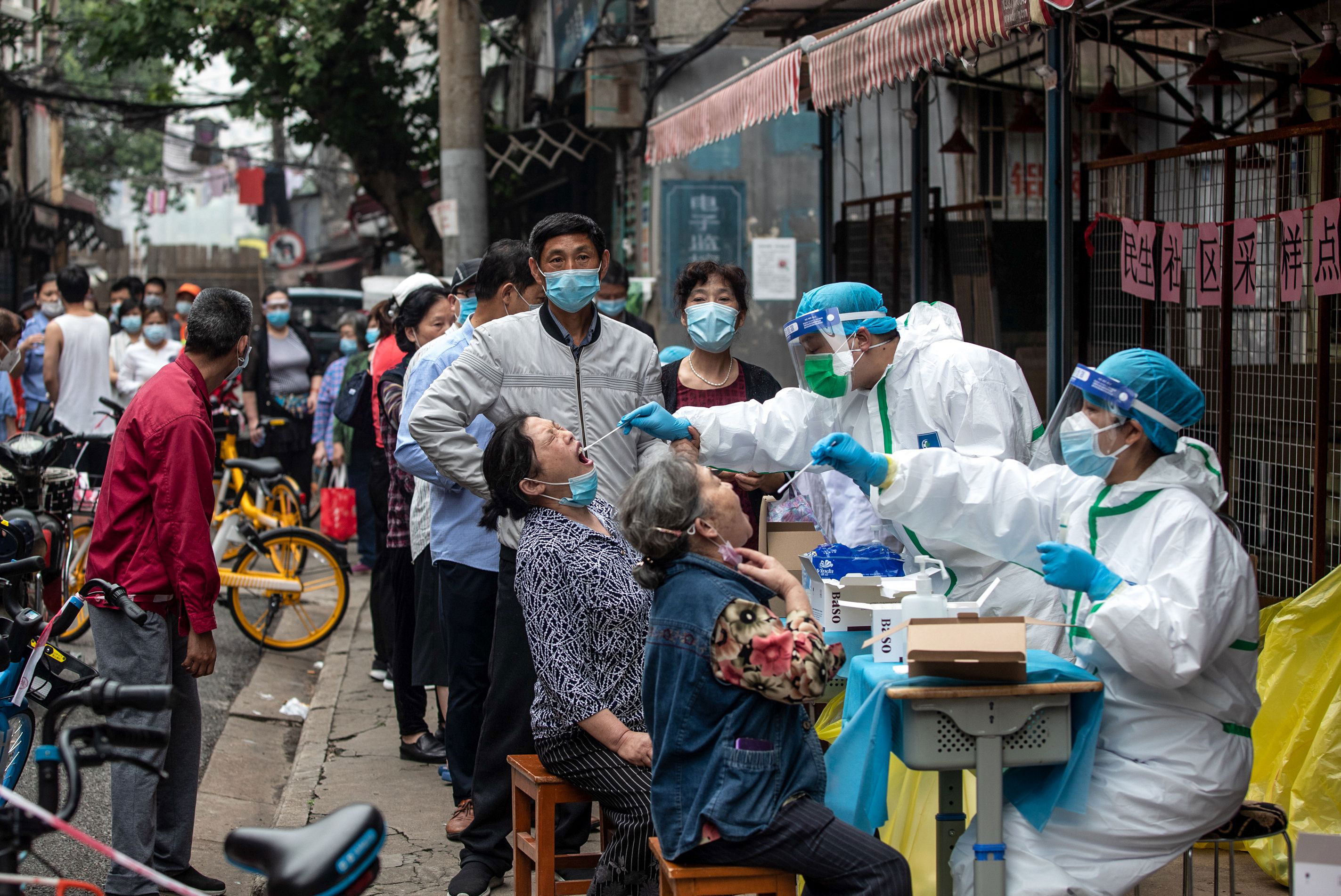 Medical workers take swab samples from residents to be tested for coronavirus on May 15 in Wuhan, China.