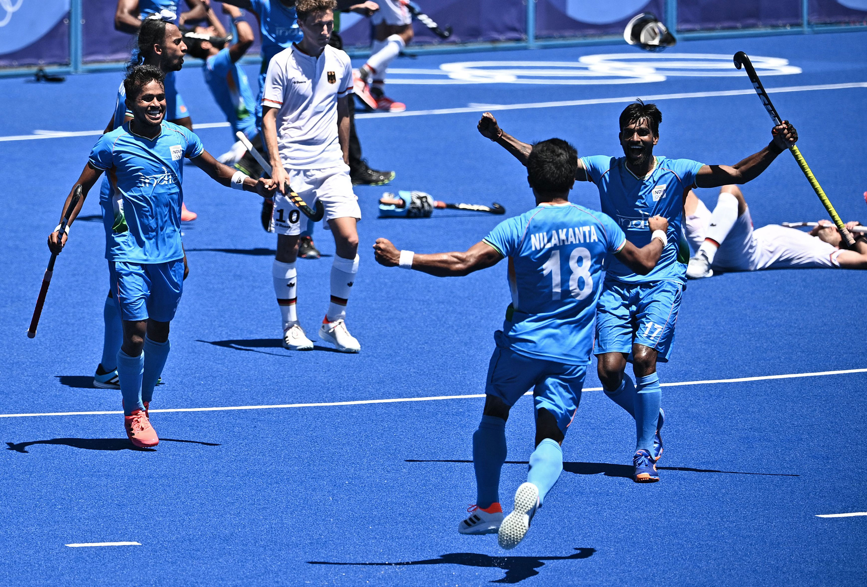 Members of India's mens field hockey team celebrate after defeating Germany for the bronze on August 5.