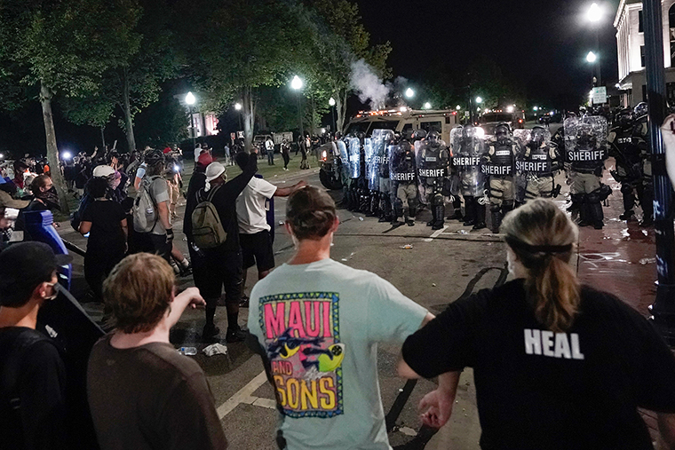Police clash with protesters near the Kenosha County Courthouse, Monday, August 24, in Kenosha, Wisconsin.