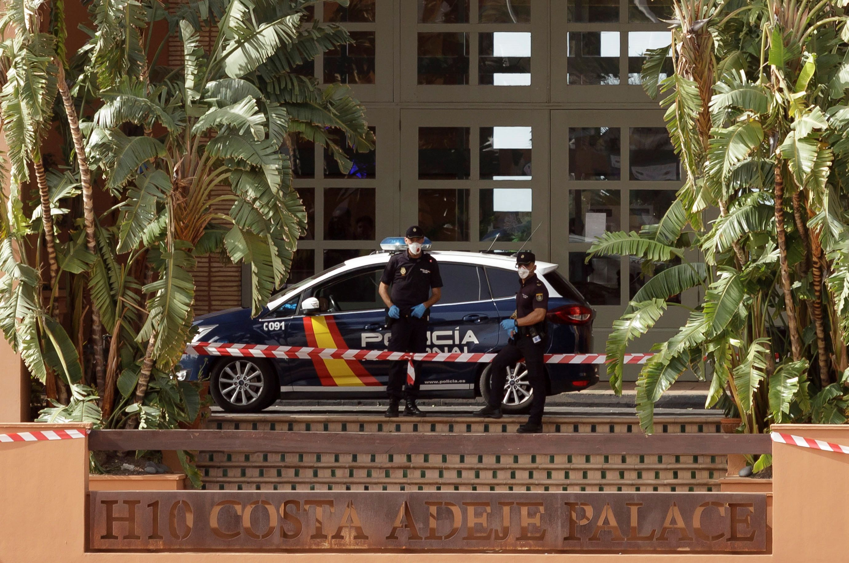 Policemen stand guard outside a hotel in Tenerife that was placed on lockdown after a guest tested positive for Coronavirus on February 25.
