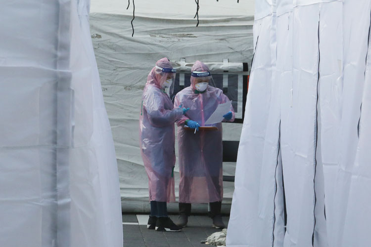 Medical staff wearing protective suits check documents as they wait for people with suspected symptoms of the novel coronavirus, at a testing facility in Seoul, on Wednesday, March 4.