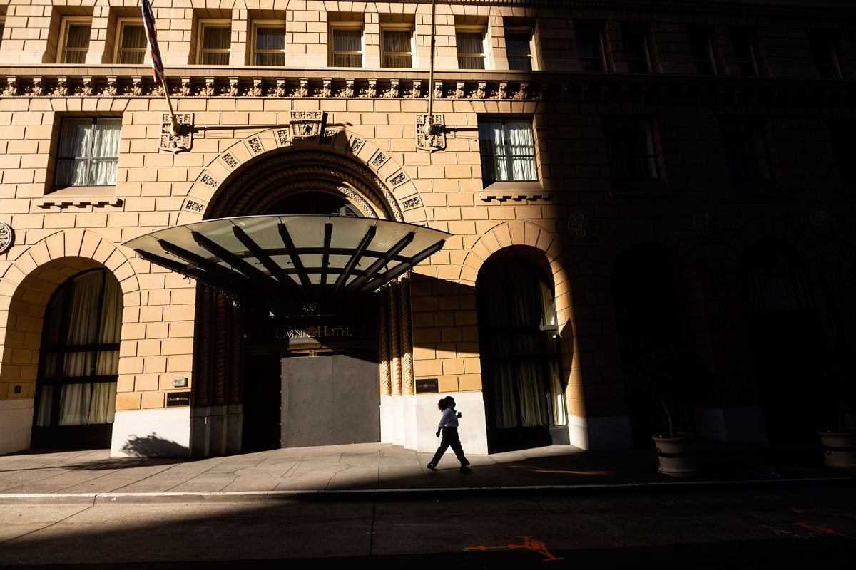 A pedestrian passes a boarded up entrance to the Omni San Francisco Hotel on October 21 in San Francisco, California.