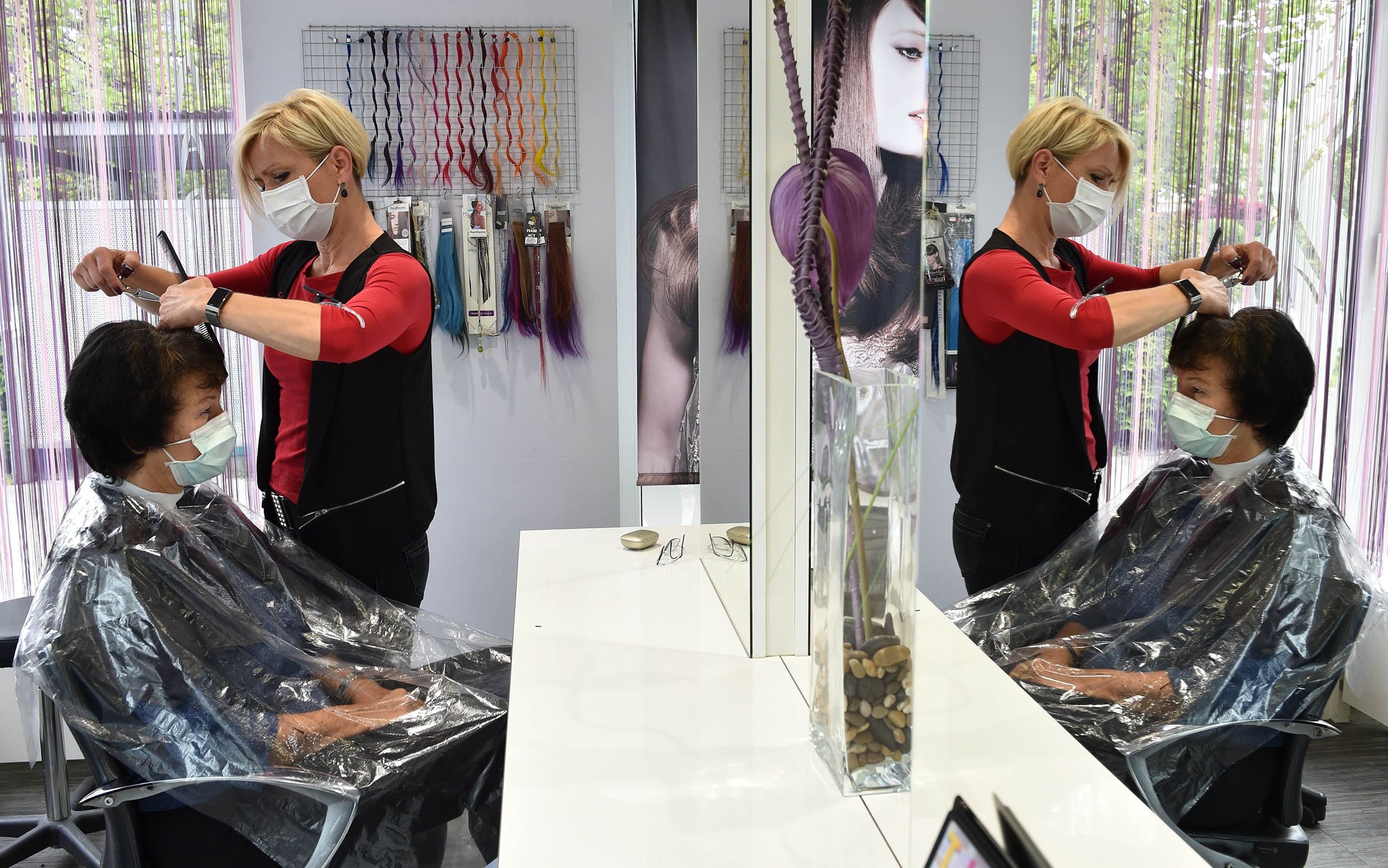 Hairdresser Andrea Macha cuts a customer's hair in her salon in Puchheim near Munich, Germany, during the first day of reopening amid the novel coronavirus pandemic on May 4.