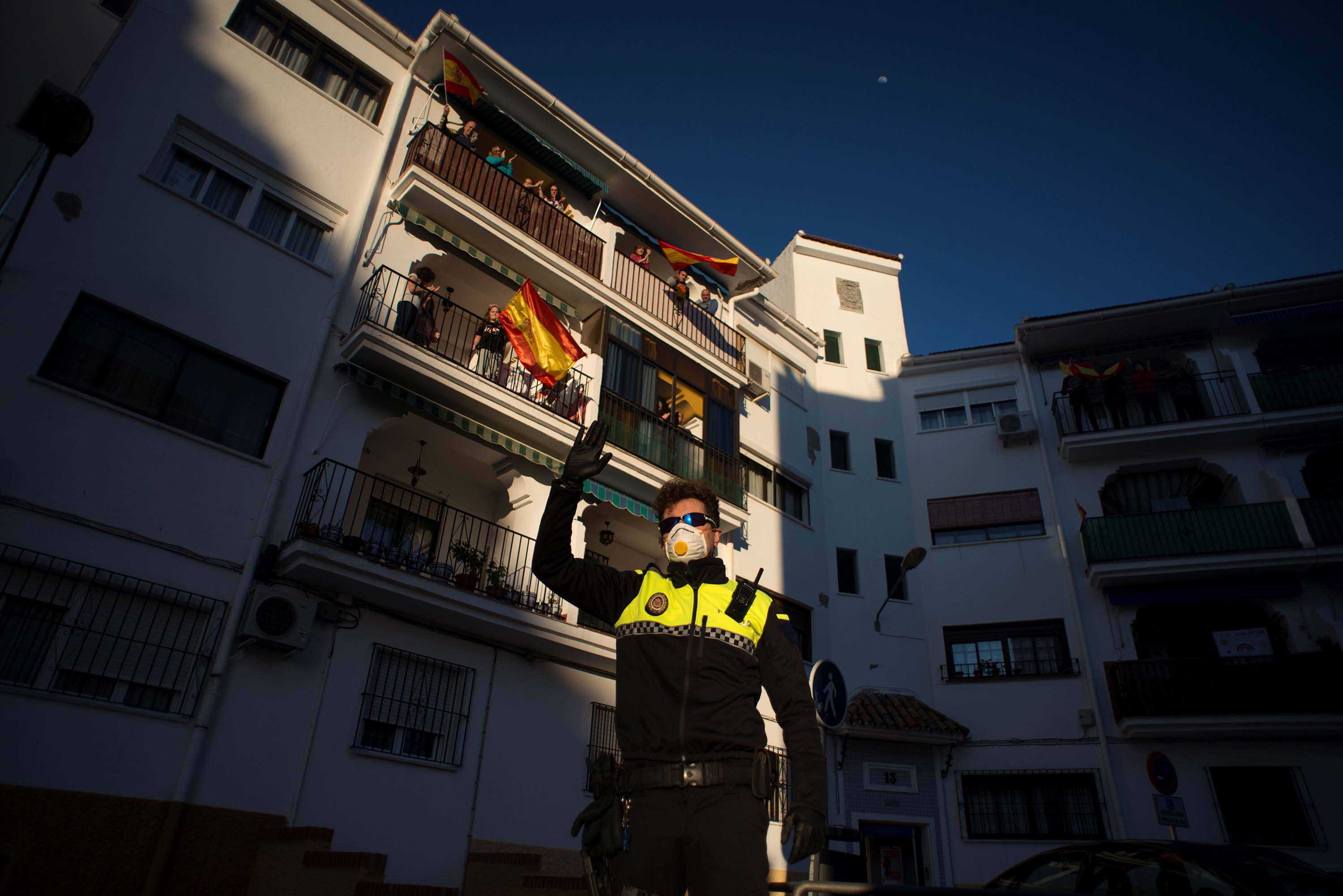A police officer waves as people applaud to thank healthcare workers dealing with the coronavirus outbreak in Ronda, Spain, on April 3.