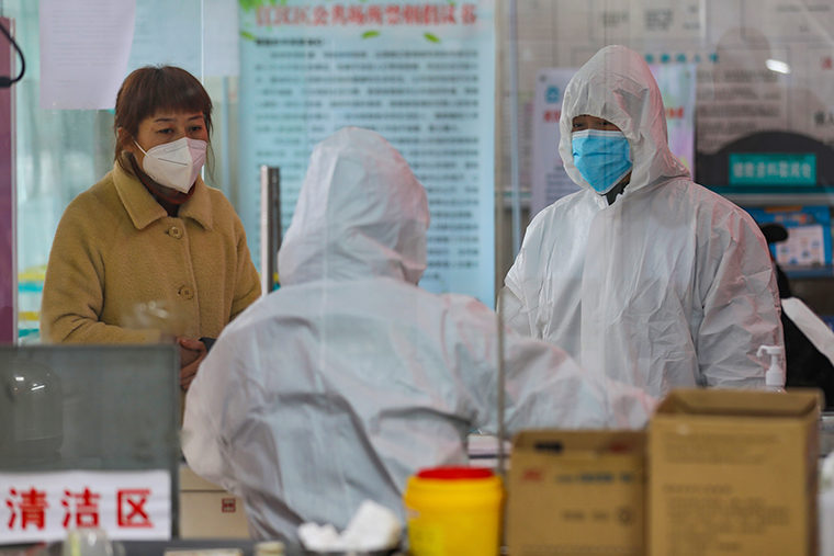 Medical workers in protective gear talk with a woman suspected of being ill at a community health station in Wuhan, China, on Monday, January 27.
