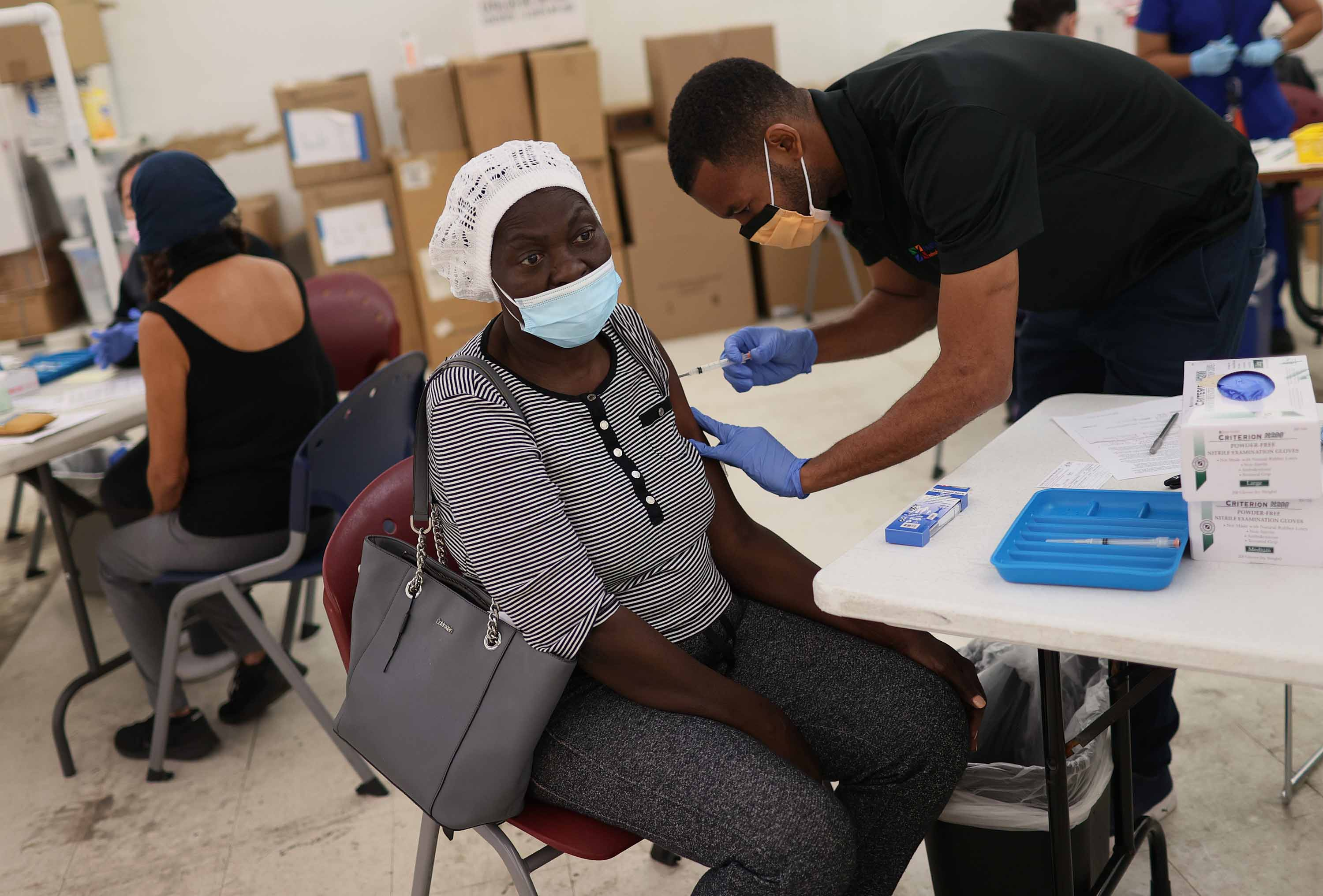 Medical Assistant Odilest Guerrier administers a Moderna COVID-19 vaccine to Marie Val at a clinic in Immokalee, Florida, on May 20.
