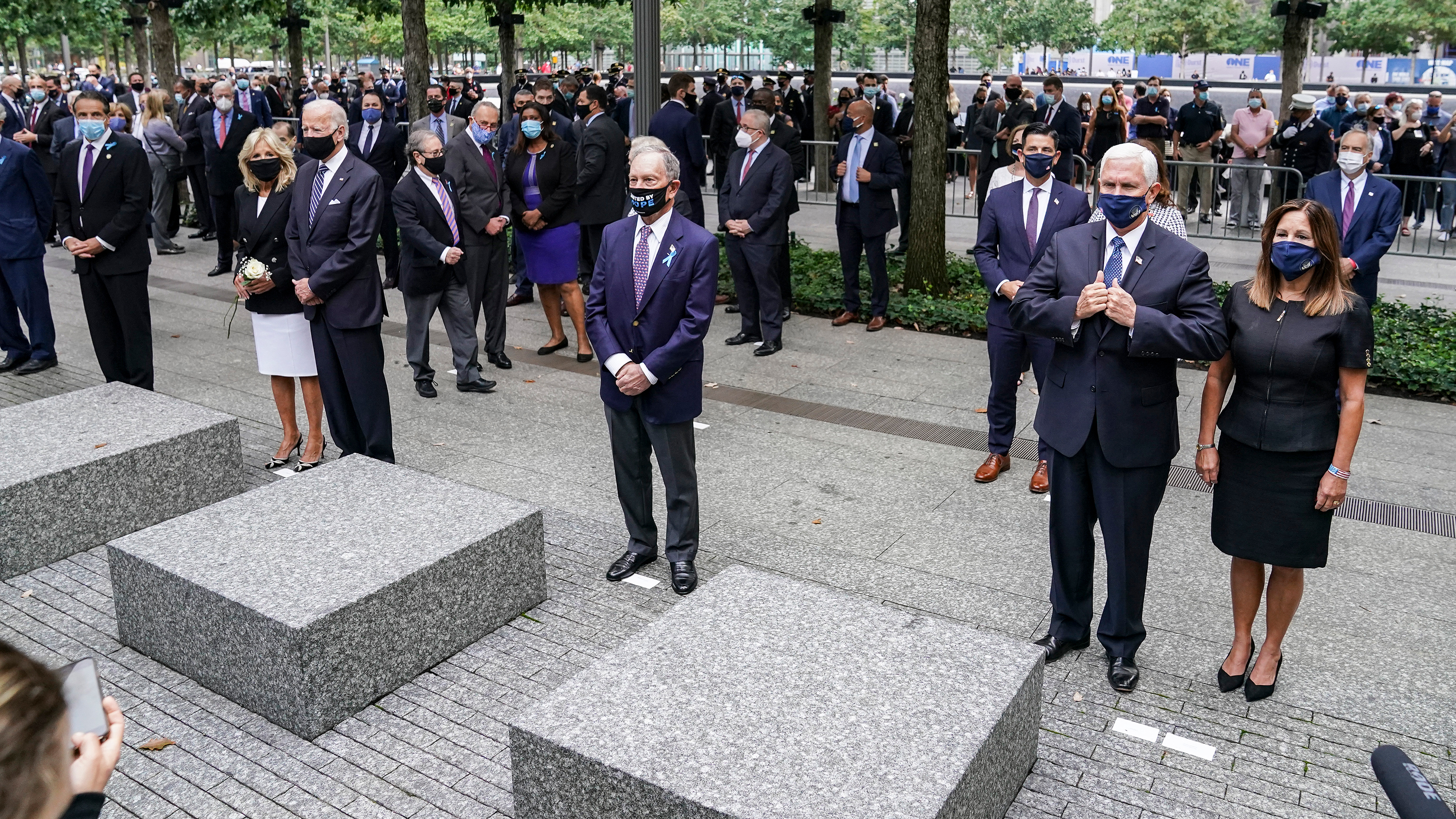 Left to right: New York Gov. Andrew Cuomo, Democratic presidential candidate Joe Biden and h, former New York Mayor Mike Bloomberg, and Vice President Mike Pence and Second Lady Karen Pence stand during the national anthem at the National September 11 Memorial and Museum, Friday, Sept. 11, 2020, in New York. Americans will commemorate 9/11 with tributes that have been altered by coronavirus precautions and woven into the presidential campaign. (AP Photo/John Minchillo)