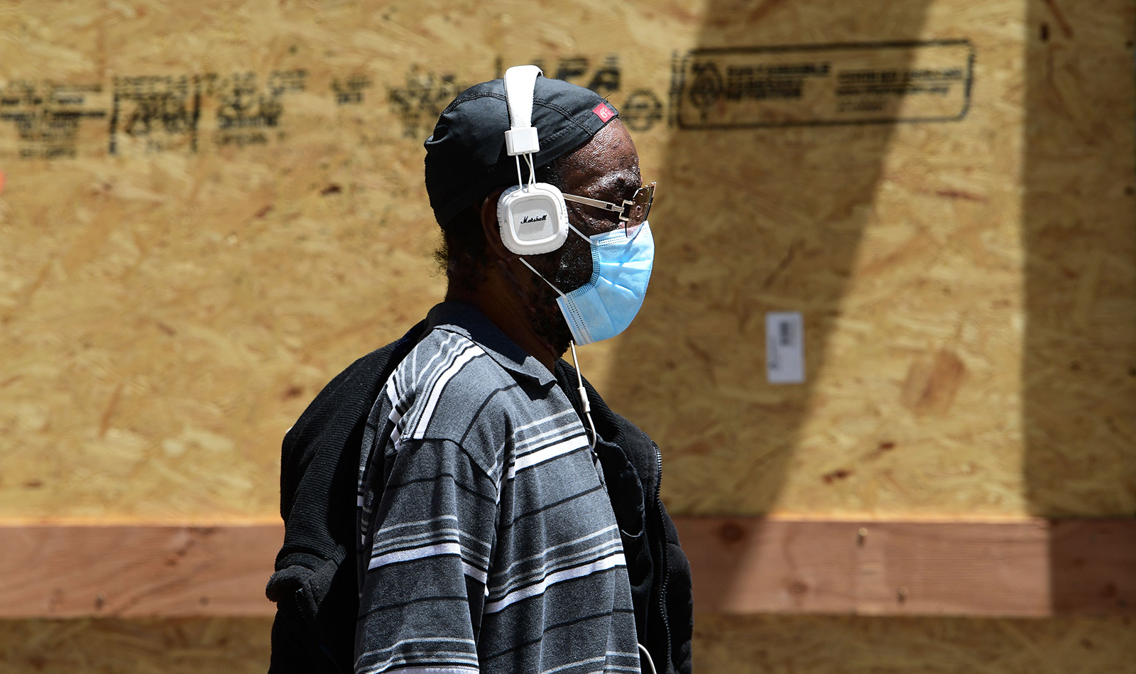 A pedestrian wears a face mask while walking past boarded up shopfronts in Los Angeles, on June 10.