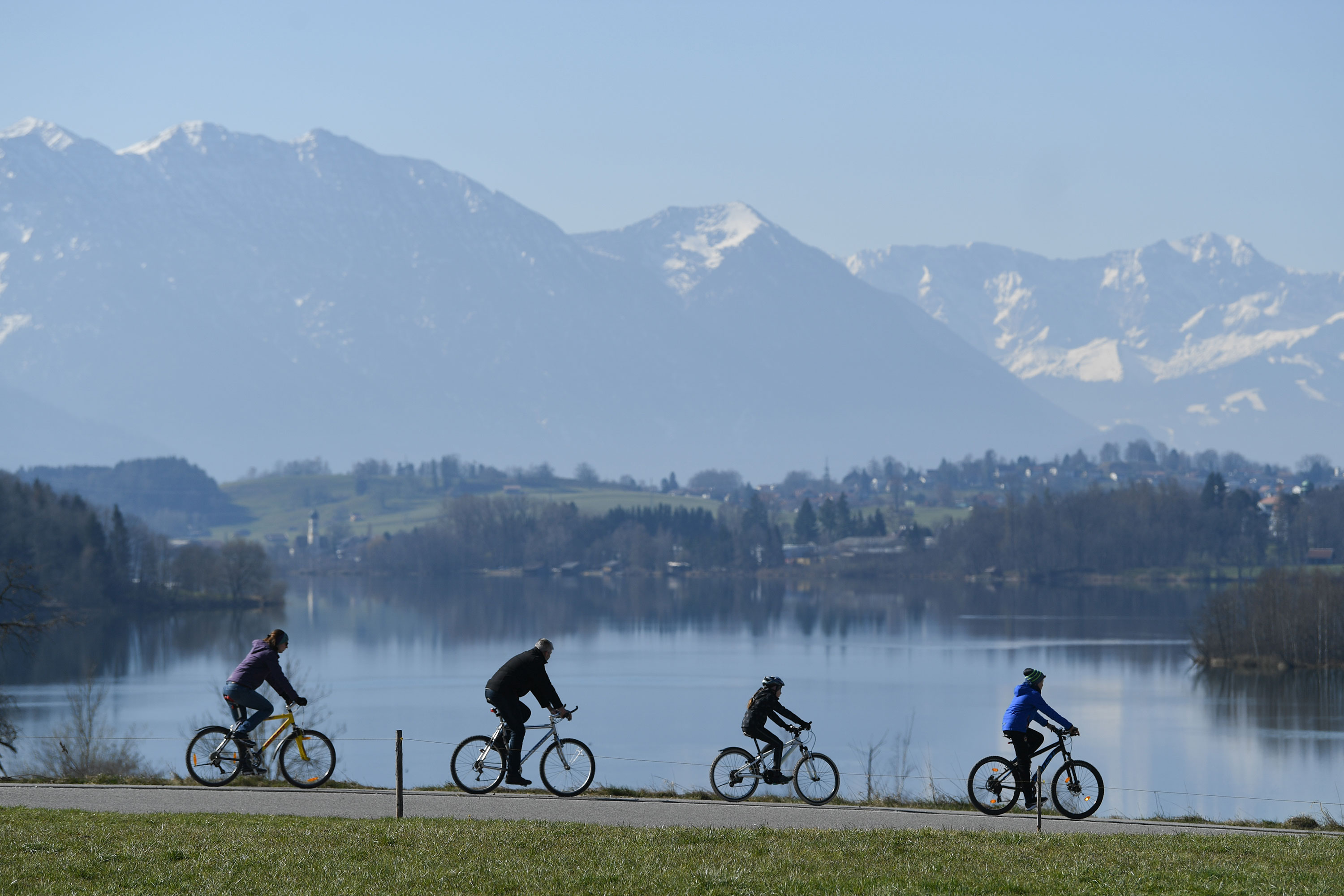 Cyclists pass Lake Riegsee in Bavaria, Germany, on April 5.