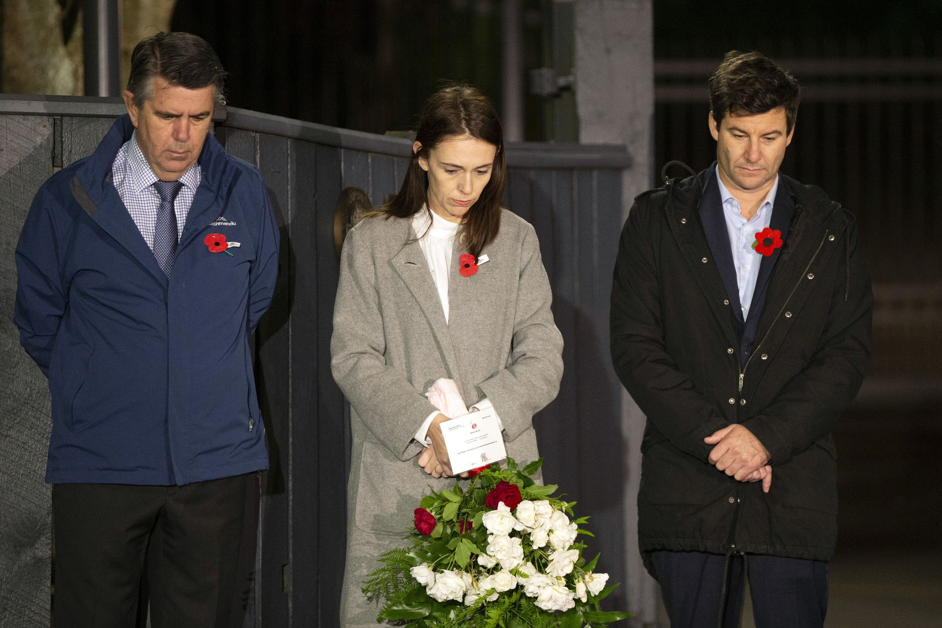 New Zealand Prime Minister Jacinda Ardern, center, with her father Ross Ardern, left, and partner Clarke Gayford stand outside Premier House in Wellington to mark Anzac Day on April 25.