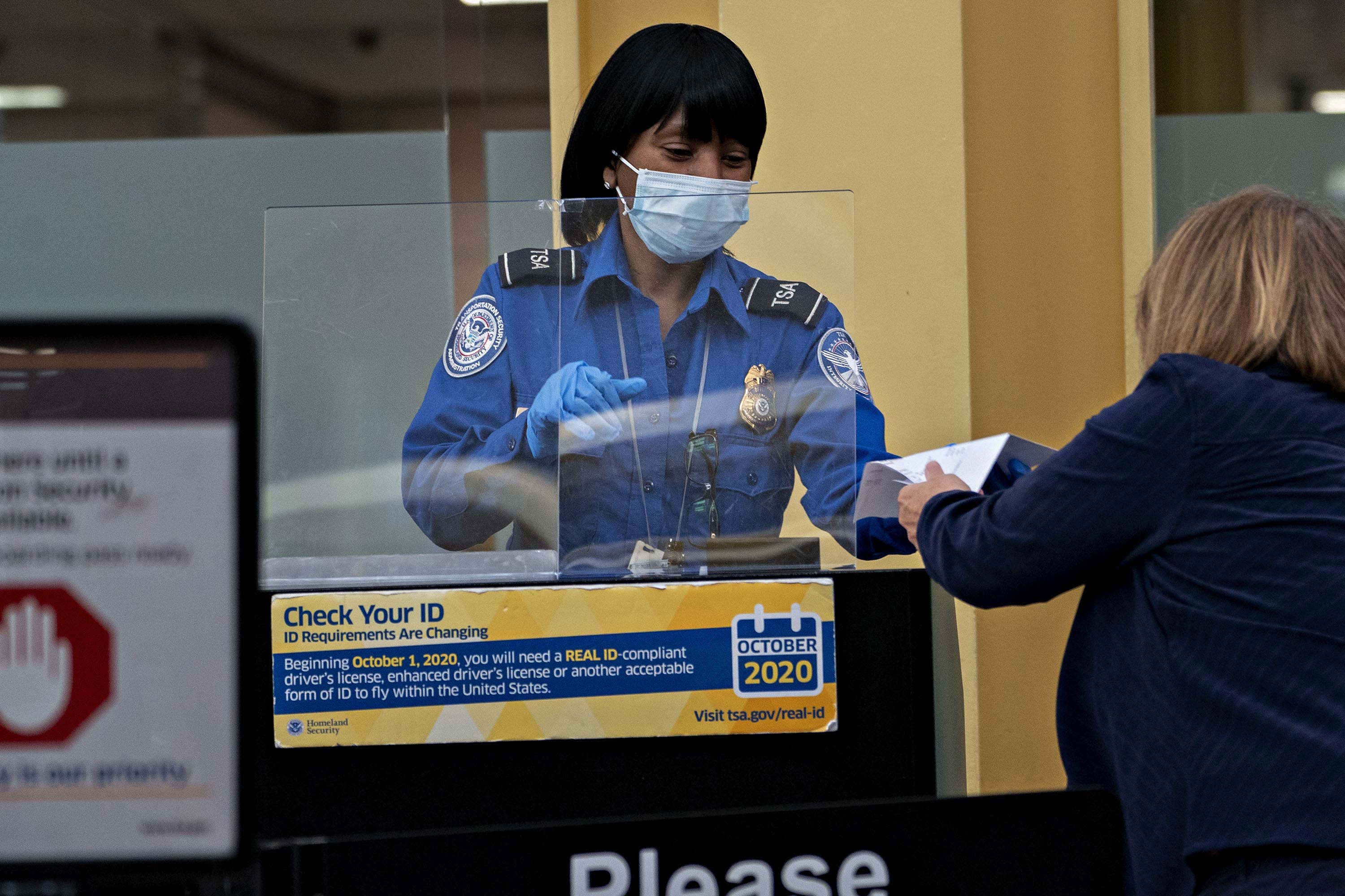 A TSA agent stands behind a protective barrier while screening a traveler at Ronald Reagan National Airport in Arlington, Virginia in June 2020.