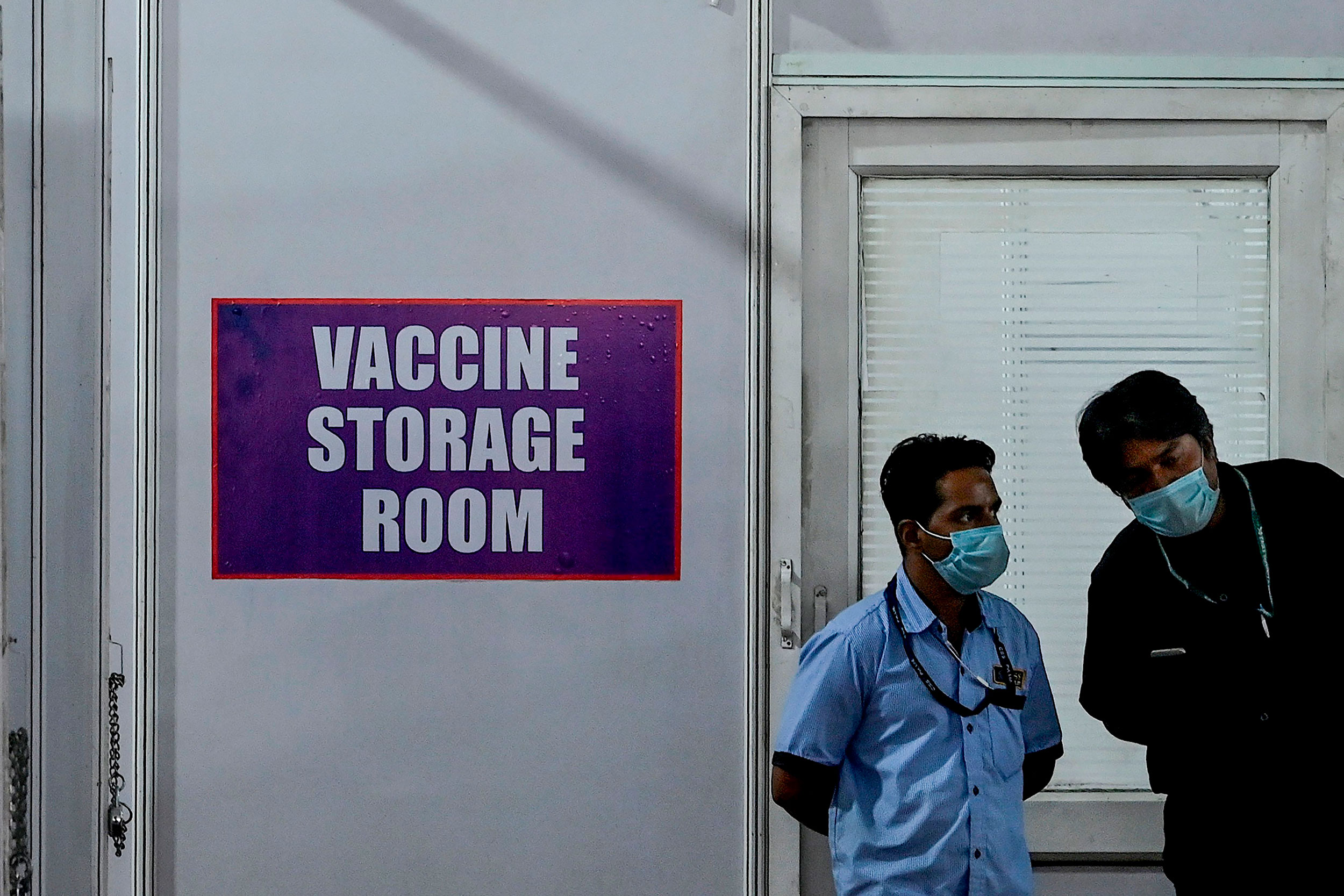 A staff member talks with security personnel outside of a storage room at a Covid-19 vaccination unit in Mumbai on January 7.