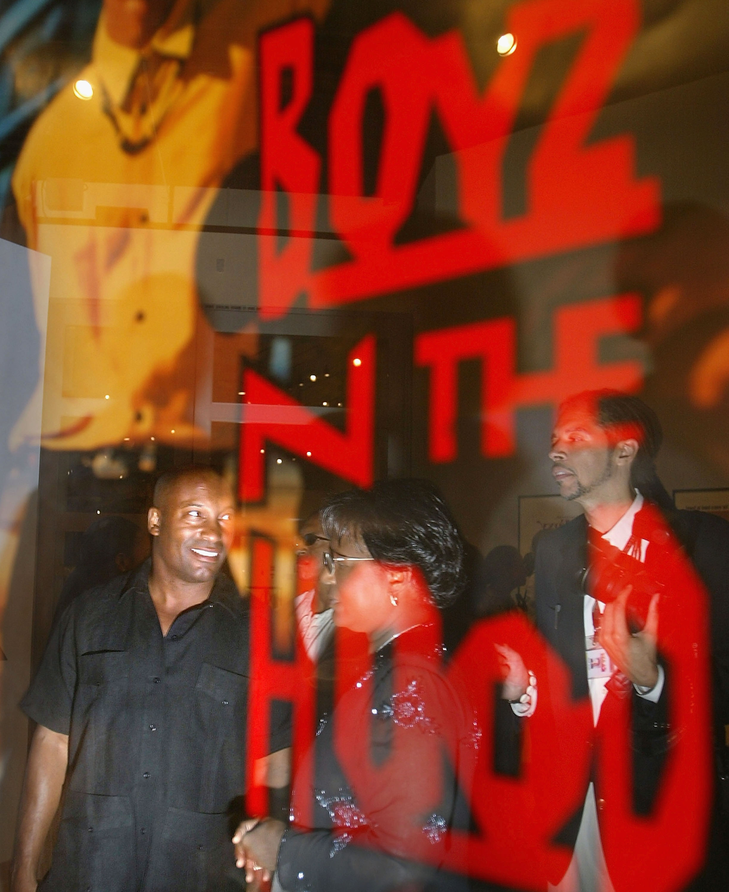 "Director John Singleton (l) is reflected in a poster for his movie ""Boyz N The Hood"" as he visits an exhibition at the California African American Museum in 2003 ."