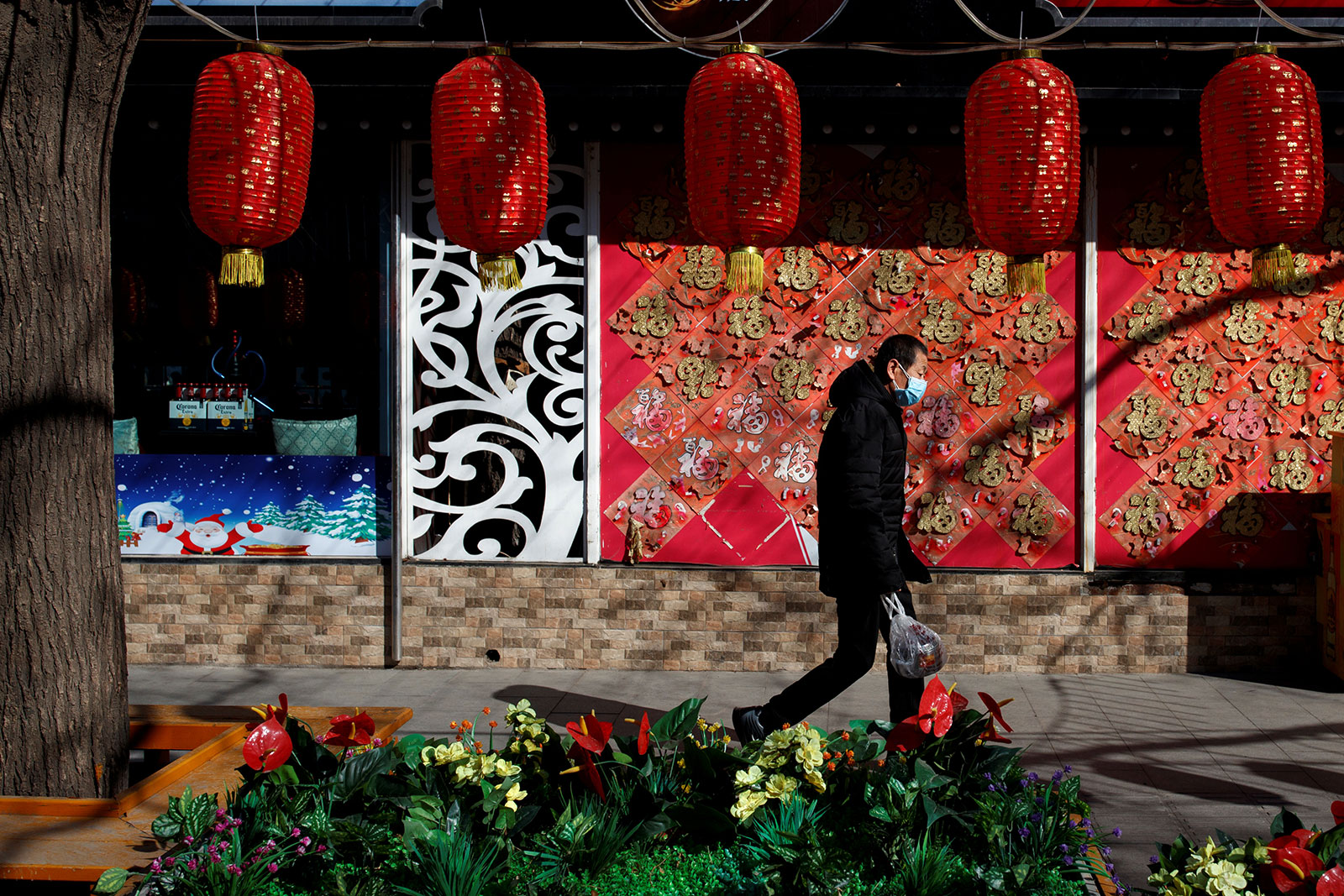 A man wearing a face mask walks past a closed restaurant in Beijing on March 4.