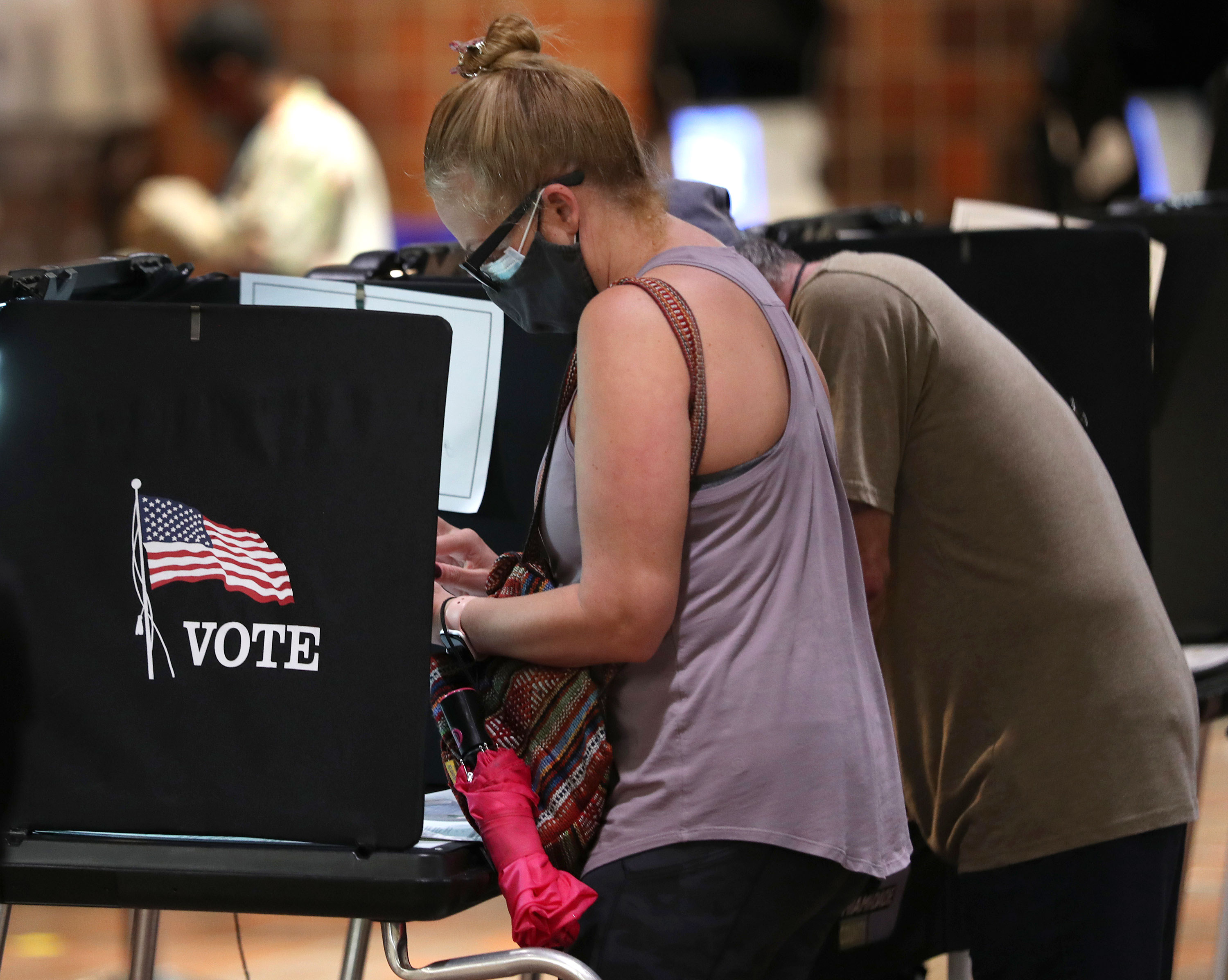 Voters fill out their ballots at the Stephen P. Clark Government Center polling station on October 21 in Miami, Florida.