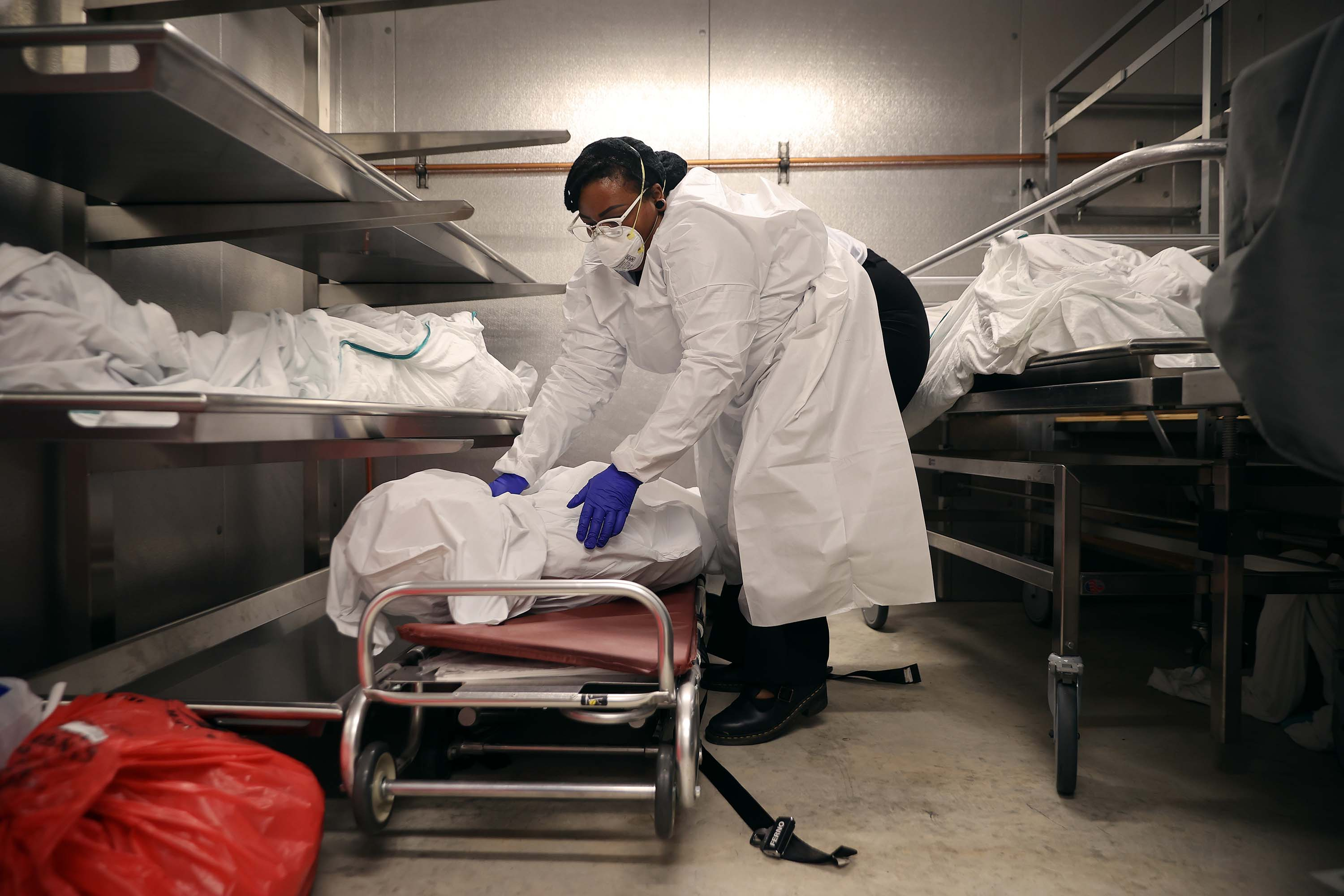 A transporter for Maryland Cremation Services moves the remains of a coronavirus victim onto a stretcher at a morgue in Silver Spring, Maryland, on May 11.