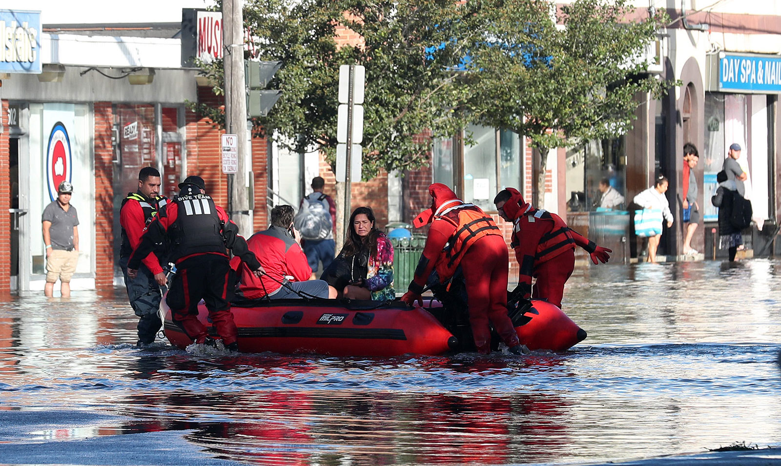 First responders pull residents in a boat as they rescue people trapped by floodwaters in Mamaroneck, New York, on September 2.