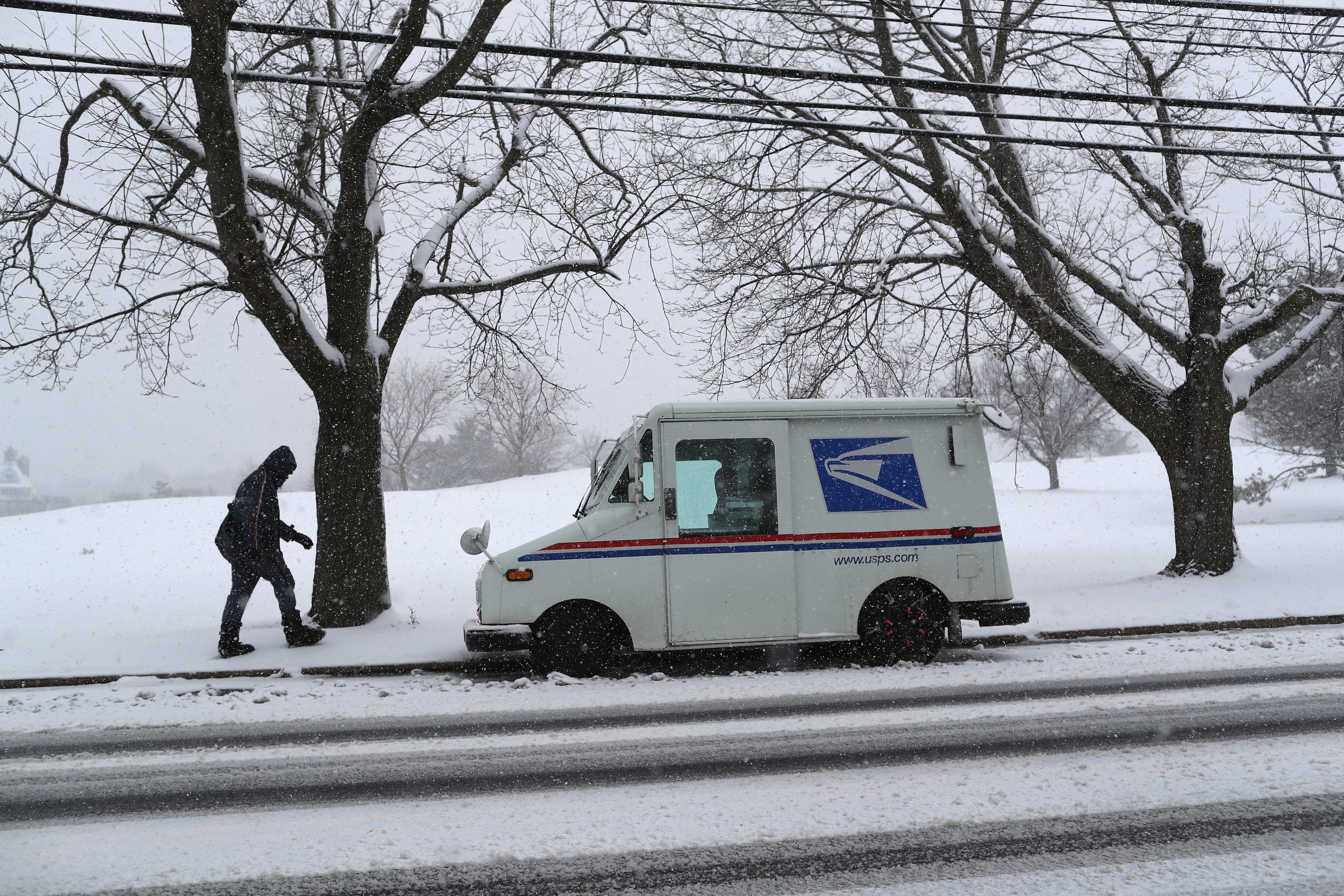 A postal worker walks through the falling snow while delivering mail on March 21, 2018. Mail service has been suspended today in parts of the Midwest.