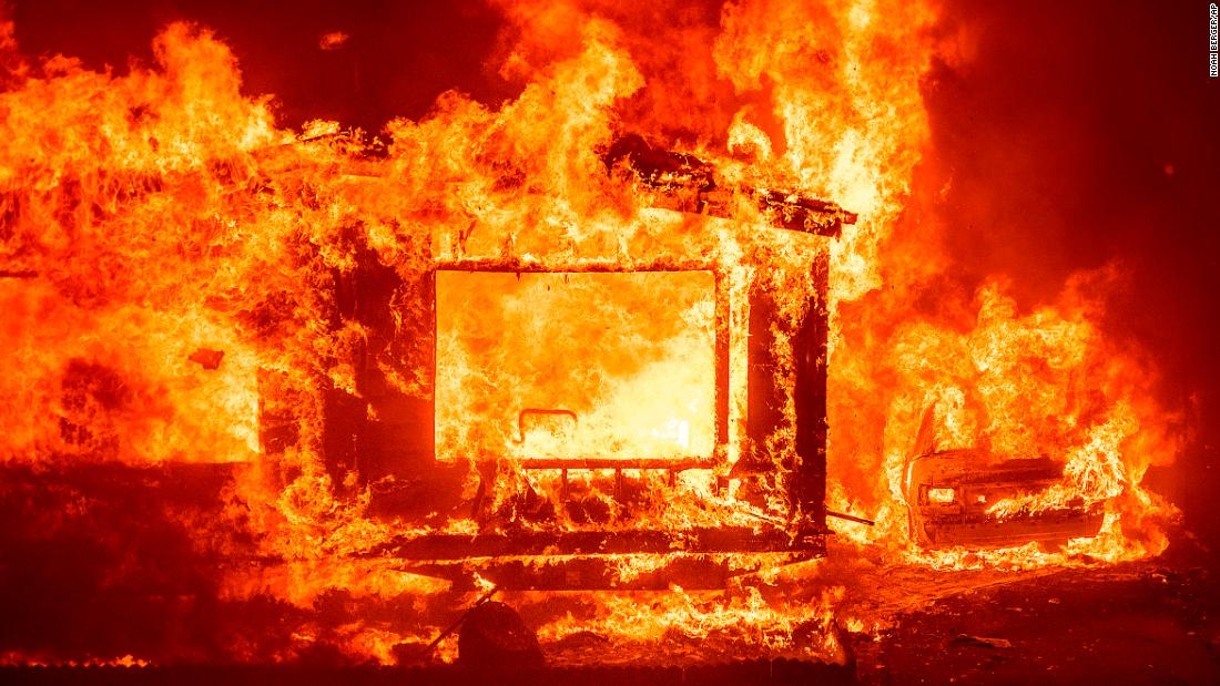 A mobile home and car burn Tuesday at Spanish Flat Mobile Villa as the LNU Complex fires tear through unincorporated Napa County, California.