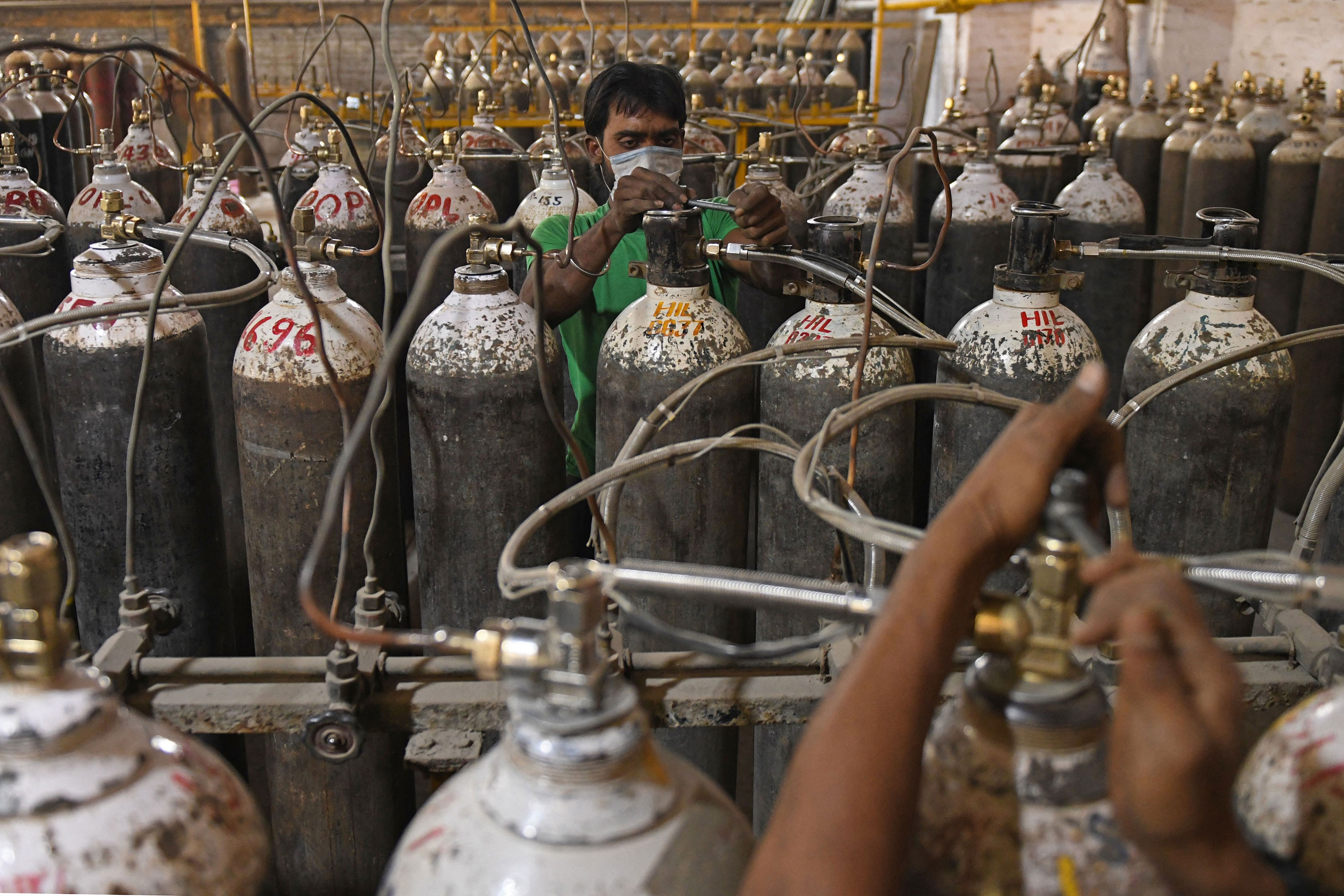 Workers sort oxygen containers at a facility on the outskirts of Amritsar, India, before dispatching them to hospitals on April 28.