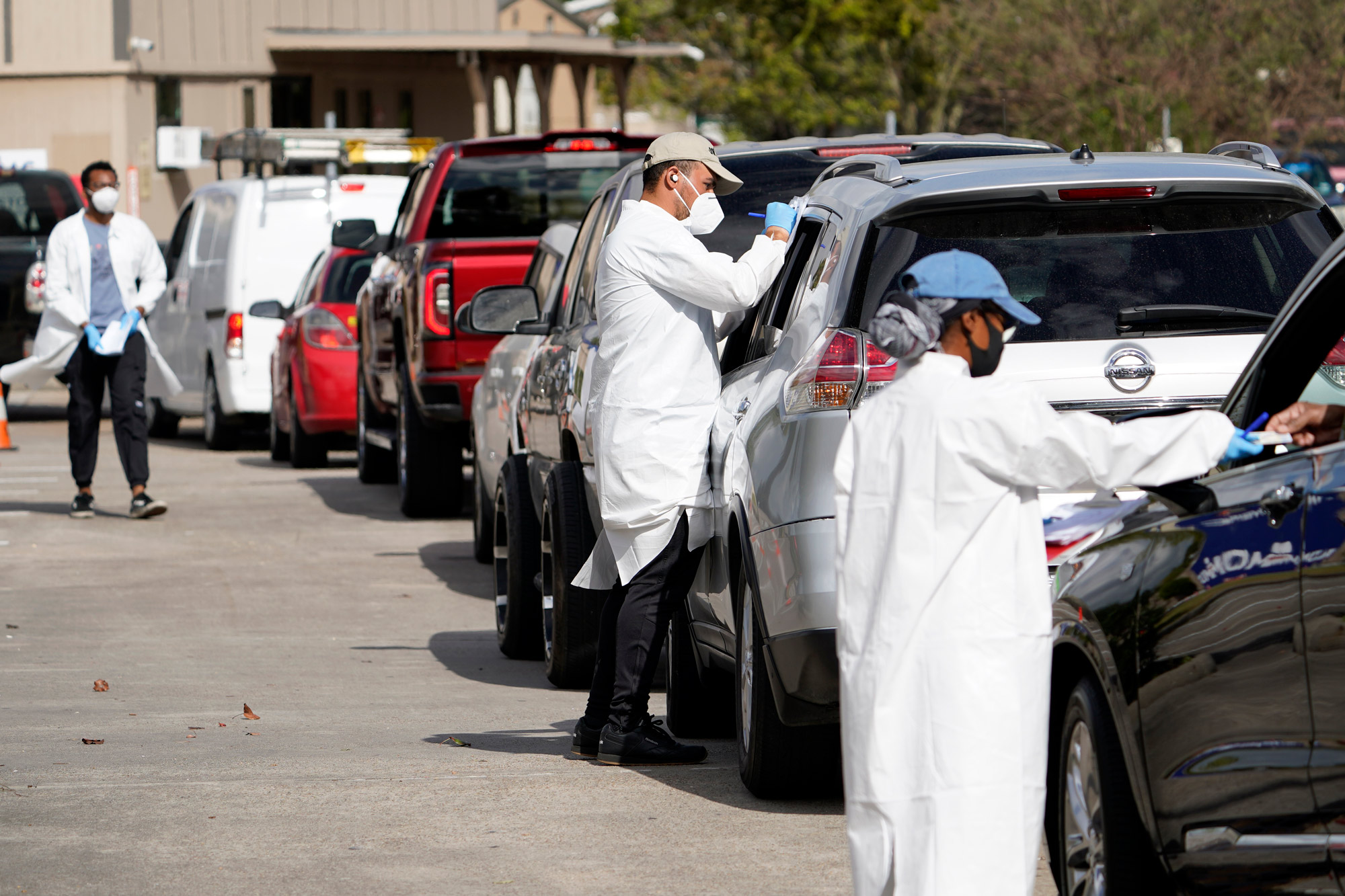 Healthcare workers process people waiting in line at a United Memorial Medical Center COVID-19 testing site on November 19 in Houston.