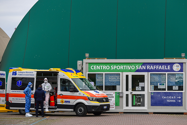 Medical workers wait by an ambulance outside a sports center where an intensive care unit was set up, near the San Raffaele hospital in Milan, on Monday, March 23.