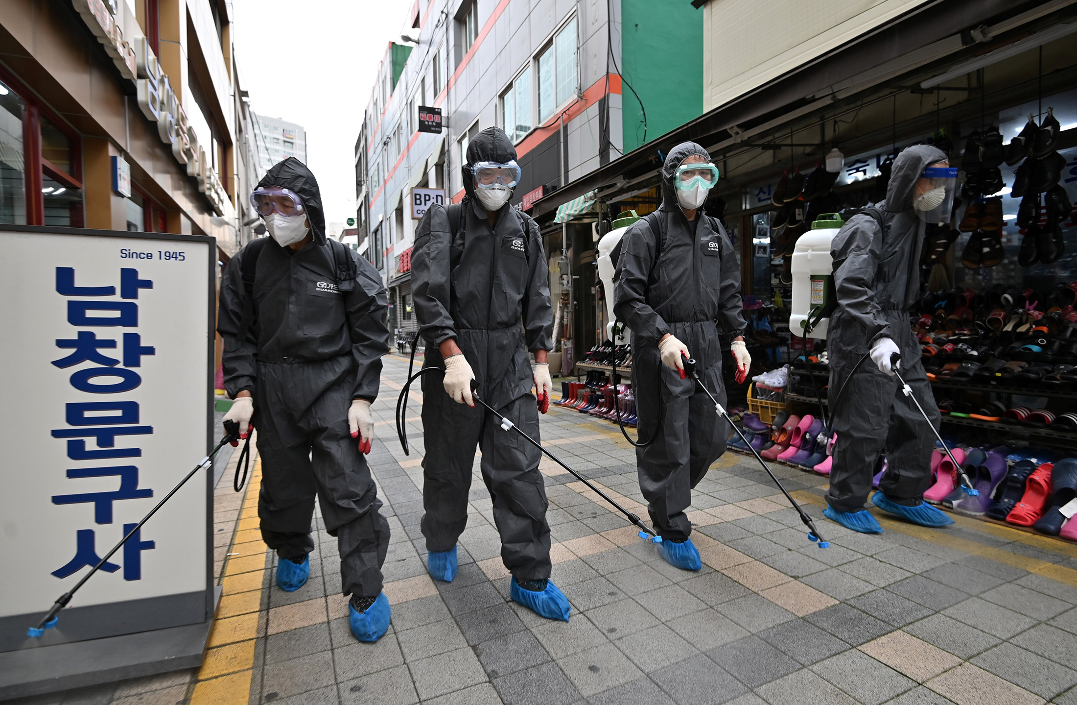 South Korean health officials from Bupyeong-gu office spray disinfectants at a shopping district in Incheon on September 17, amid the new COVID-19 coronavirus pandemic.