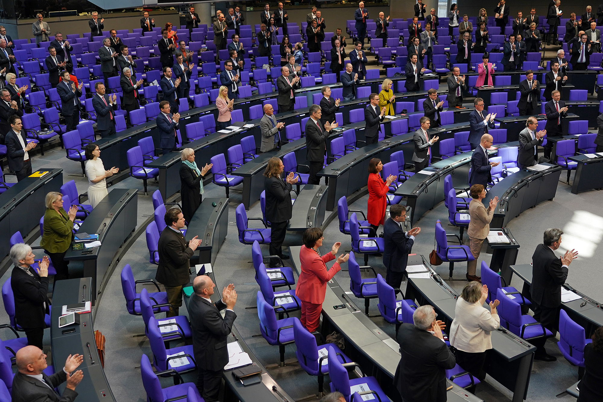 Members of the Bundestag rise to applaud medical and emergency workers on the front line of the nationwide struggle against the coronavirus prior to debates and the likely passing of a massive federal financial aid package to shore Germany up against the effects of the virus on March 25 in Berlin.