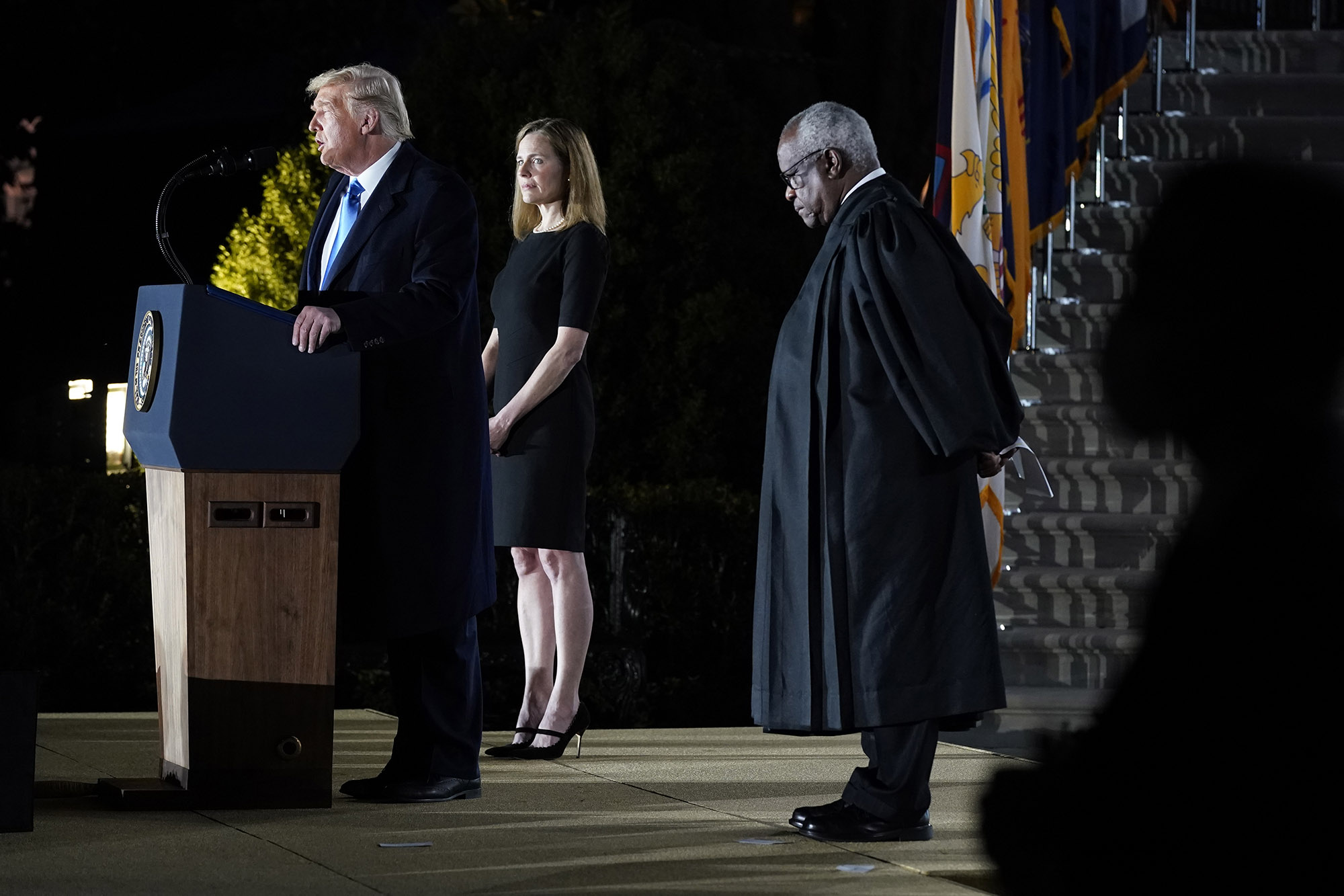 President Donald Trump speaks as Amy Coney Barrett looks on, before Supreme Court Justice Clarence Thomas, right, administers the Constitutional Oath to her on the South Lawn of the White House in Washington on Monday.