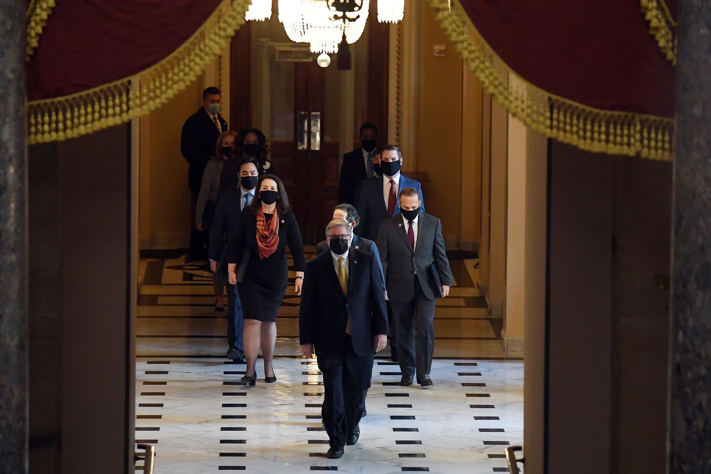 The House Sergeant of Arms (front) walks with House impeachment managers to the Senate floor as they arrive for the start of the trial of former US President Donald Trump on Capitol Hill on February 9, 2021.