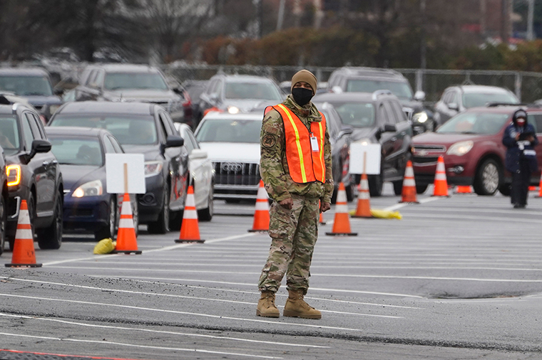 A member of the Georgia National guard helps manage traffic at a COVID-19 mass vaccination site at the Delta Flight Museum, Monday, February 22, in Atlanta. The state has four sites located around Georgia.
