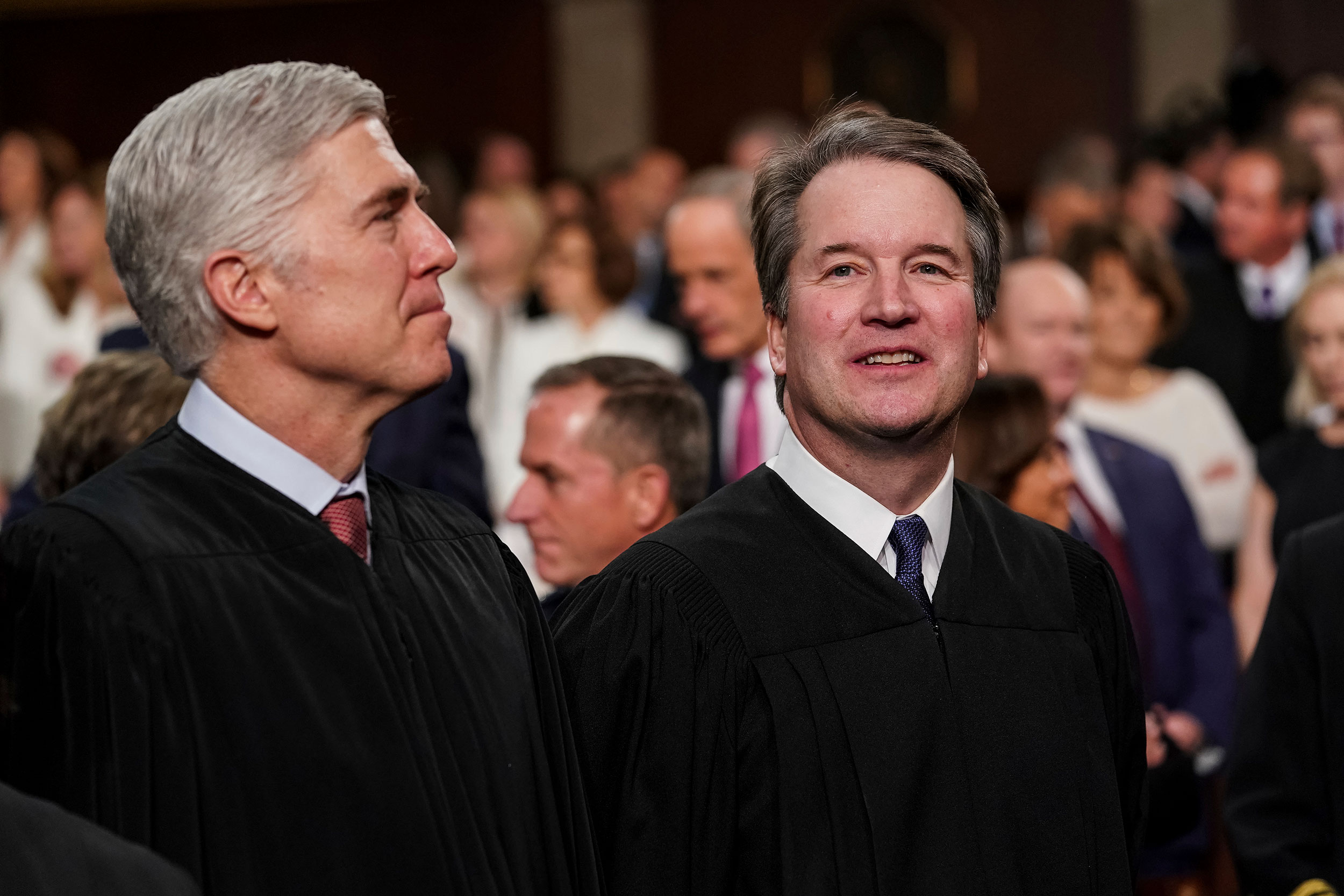 From left, Supreme Court Justices Neil Gorsuch and Brett Kavanaugh stand together at President Trump's State of the Union address on February 5, 2019.