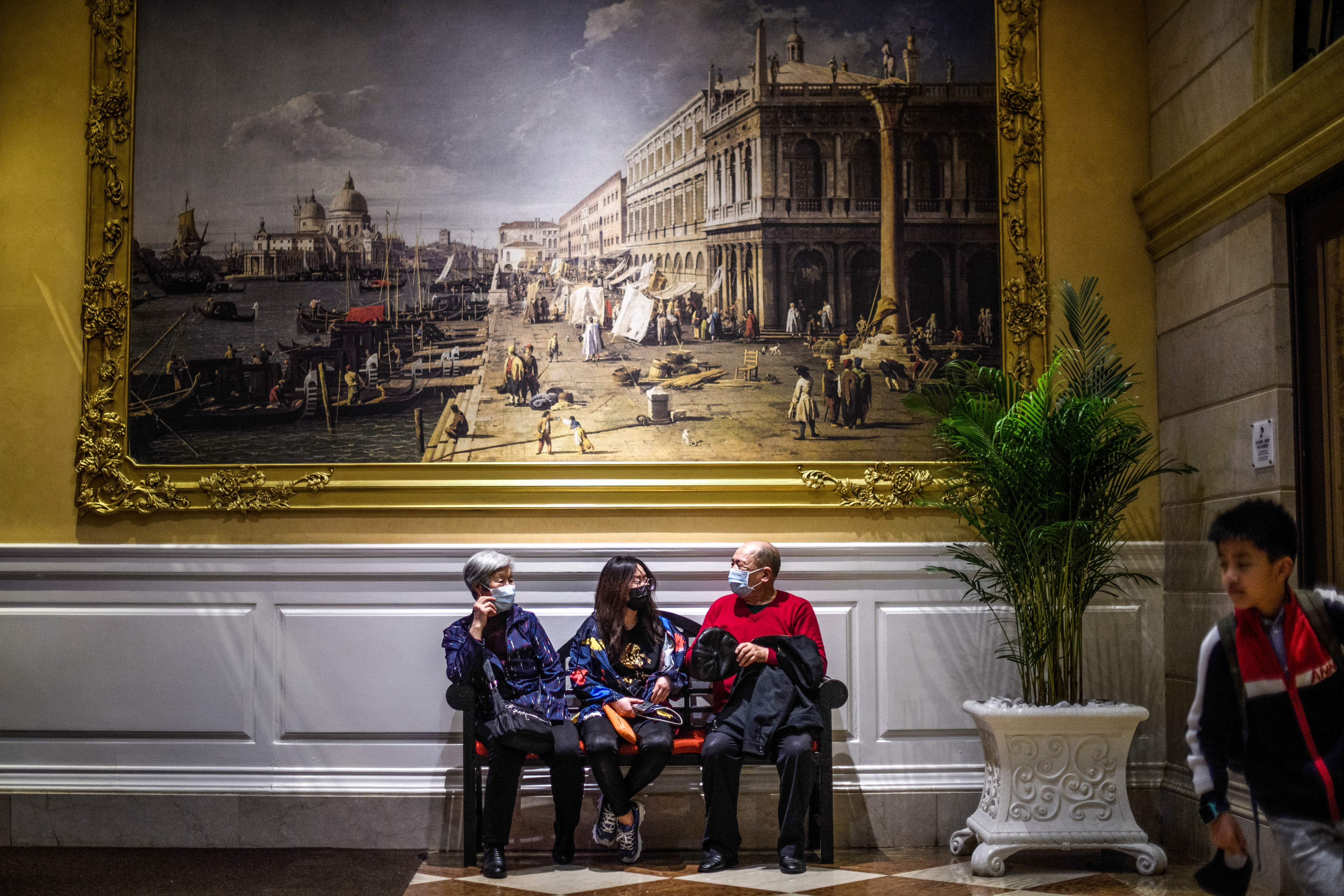 Visitors wear face masks as they sit inside the Venetian casino hotel resort in Macao on Wednesday.