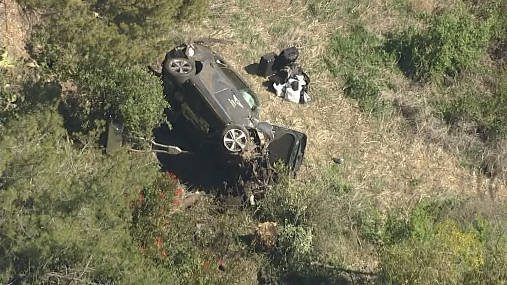 A car sits on its side at the believed car accident scene involving Tiger Woods in Rancho Palos Verdes, California, on February 23.